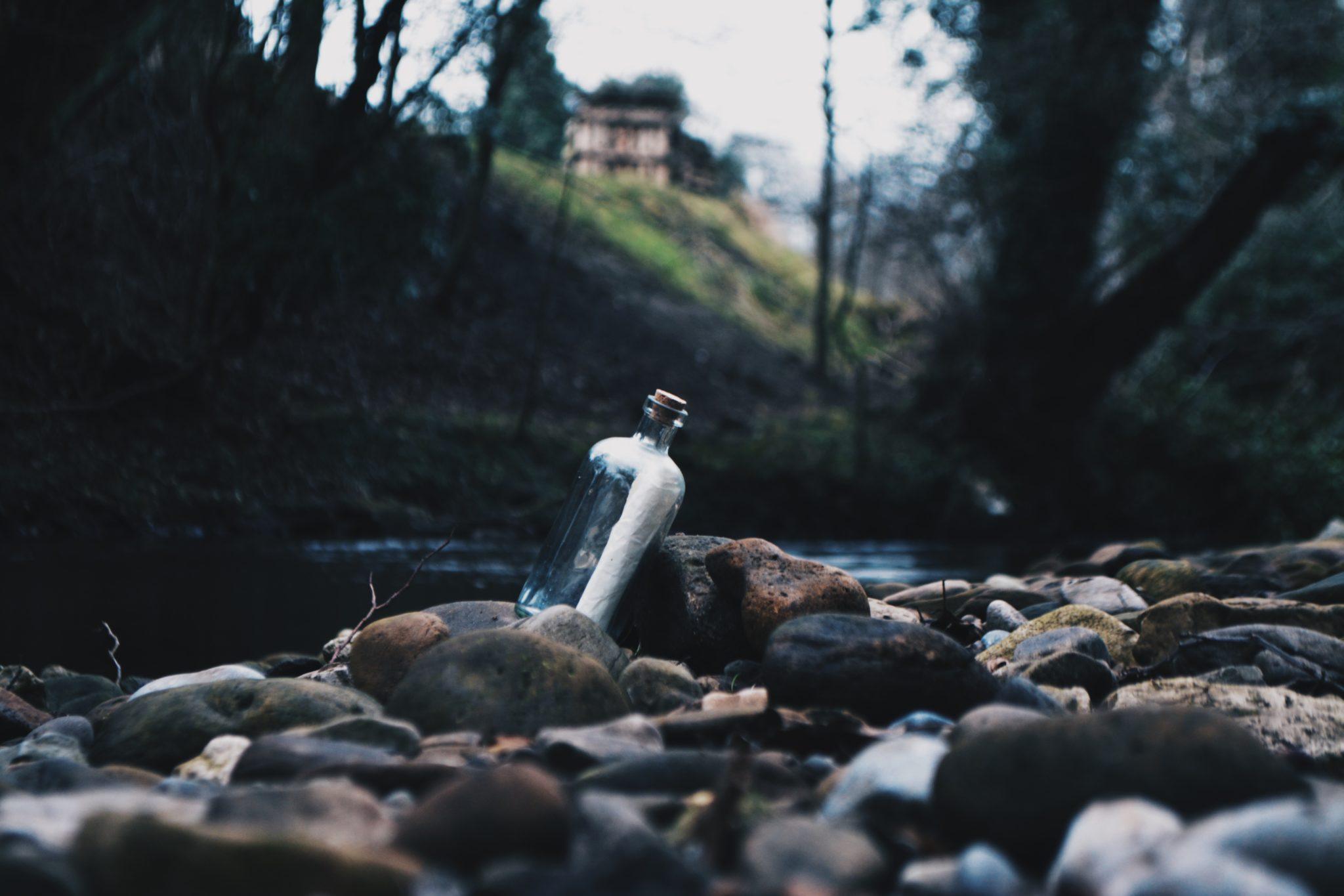 Eine Glasflasche am Ufer eines Flüsschens.