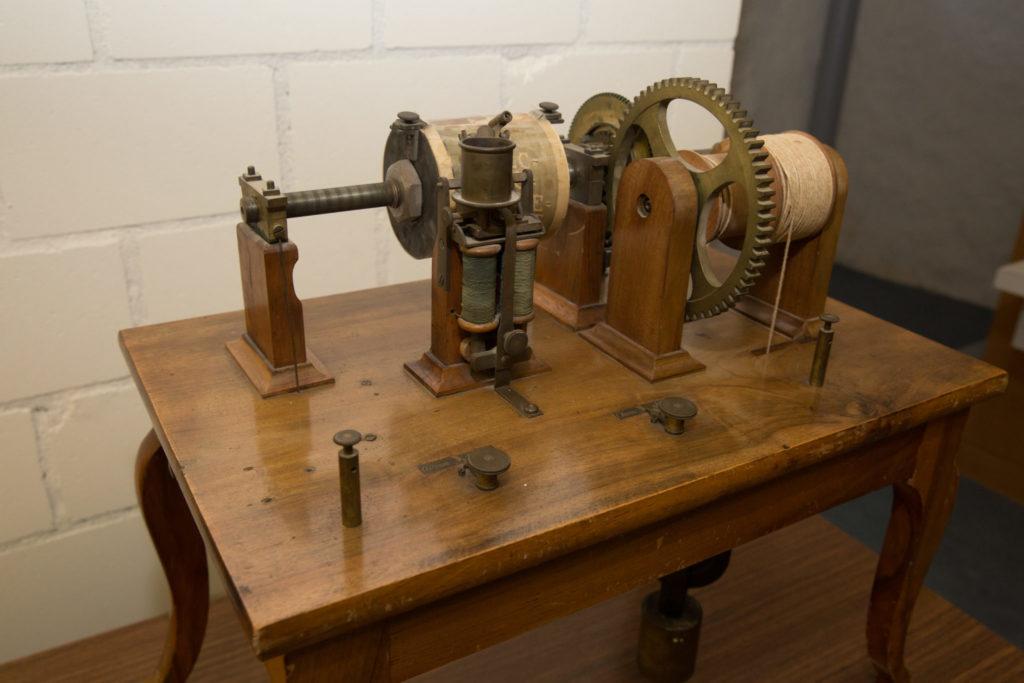 Der Typotelegraf: Eine Maschine mit einer Walze und Zahnrädern auf einem Holztisch.
