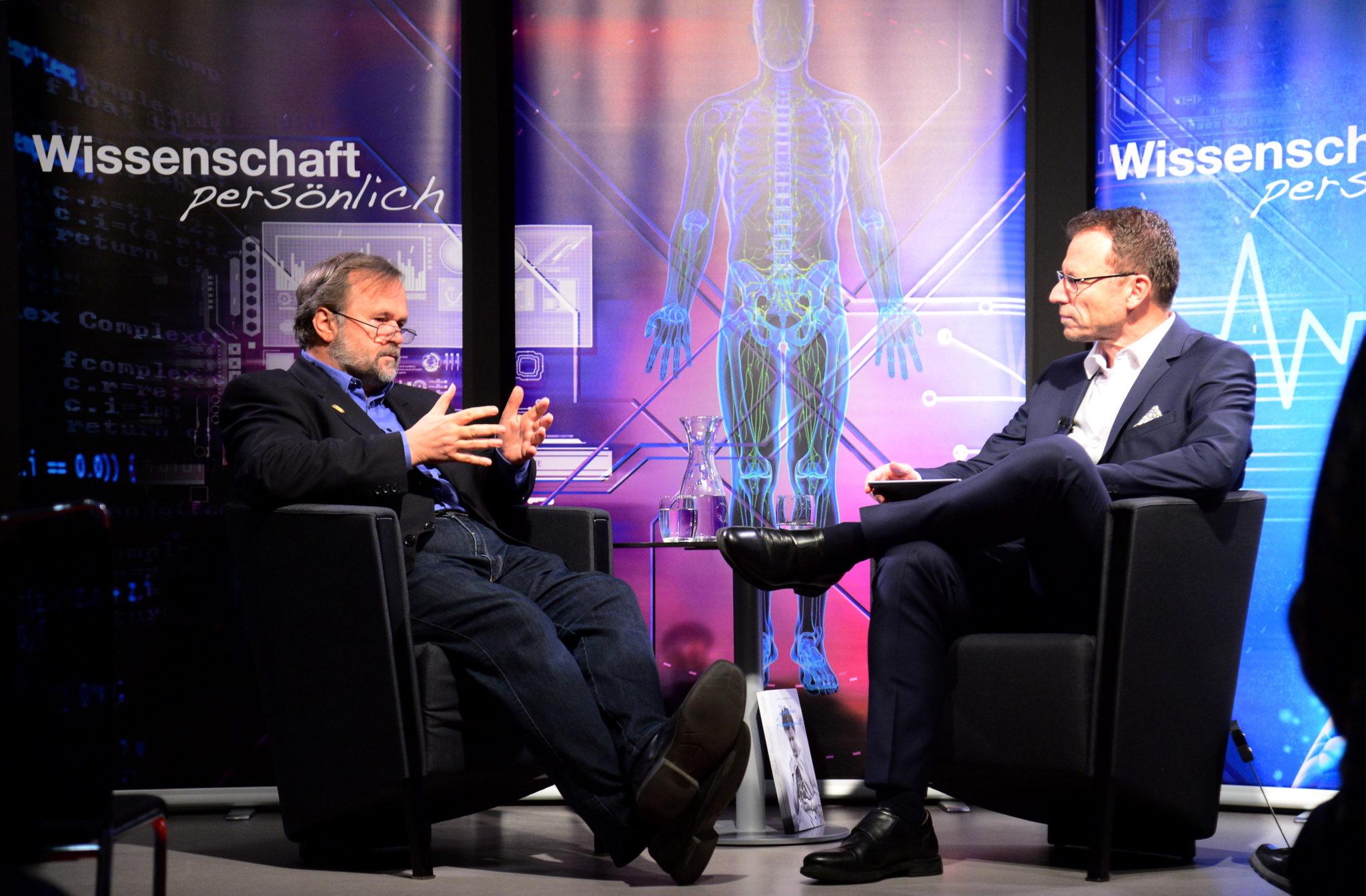 Willibald Ruch redet mit Beat Glogger. Beide sitzen sich in Sesseln gegenüber.