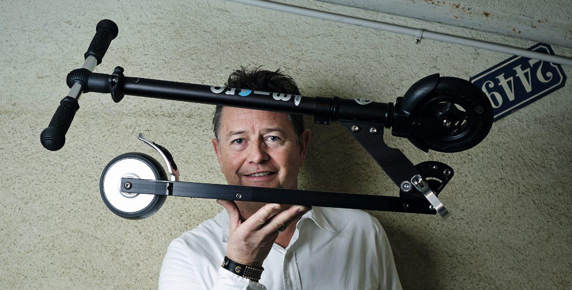Wim Ouboter hält eines seiner Microlino-Mini-Trottinetts vor sein Gesicht.
