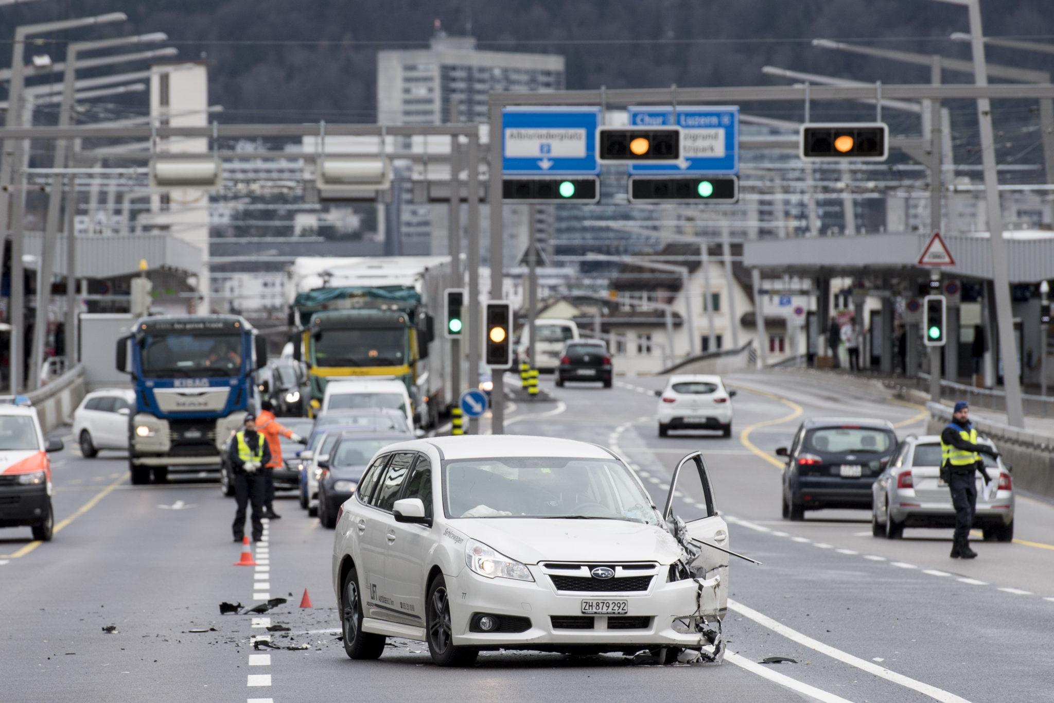 Ein weisses Auto steht auf der Handdrücke in Zürich, links vorne ist es von einer Kollision eingedrückt. Polizisten dirigieren den Verkehr um das verunfallte Auto herum.