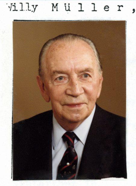 Foto von Willy Müller, älterer Herr mit grauem Kurzhaarschnitt, verschmitzte Lächeln, Anzug.