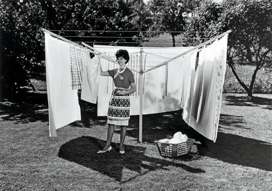 Ein Schwarz-Weiss-Foto aus den späten 50er-Jahren. Zu sehen ist eine Frau, die im Garten steht und am Stewi Wäsche aufhängt.