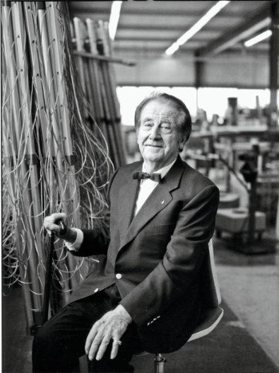 Walter Steiner, ein älterer Herr mit Gehstock und Fliege, sitzt leicht lächelnd neben ein paar zusammengefalteten Stewis in einer Fabrik.