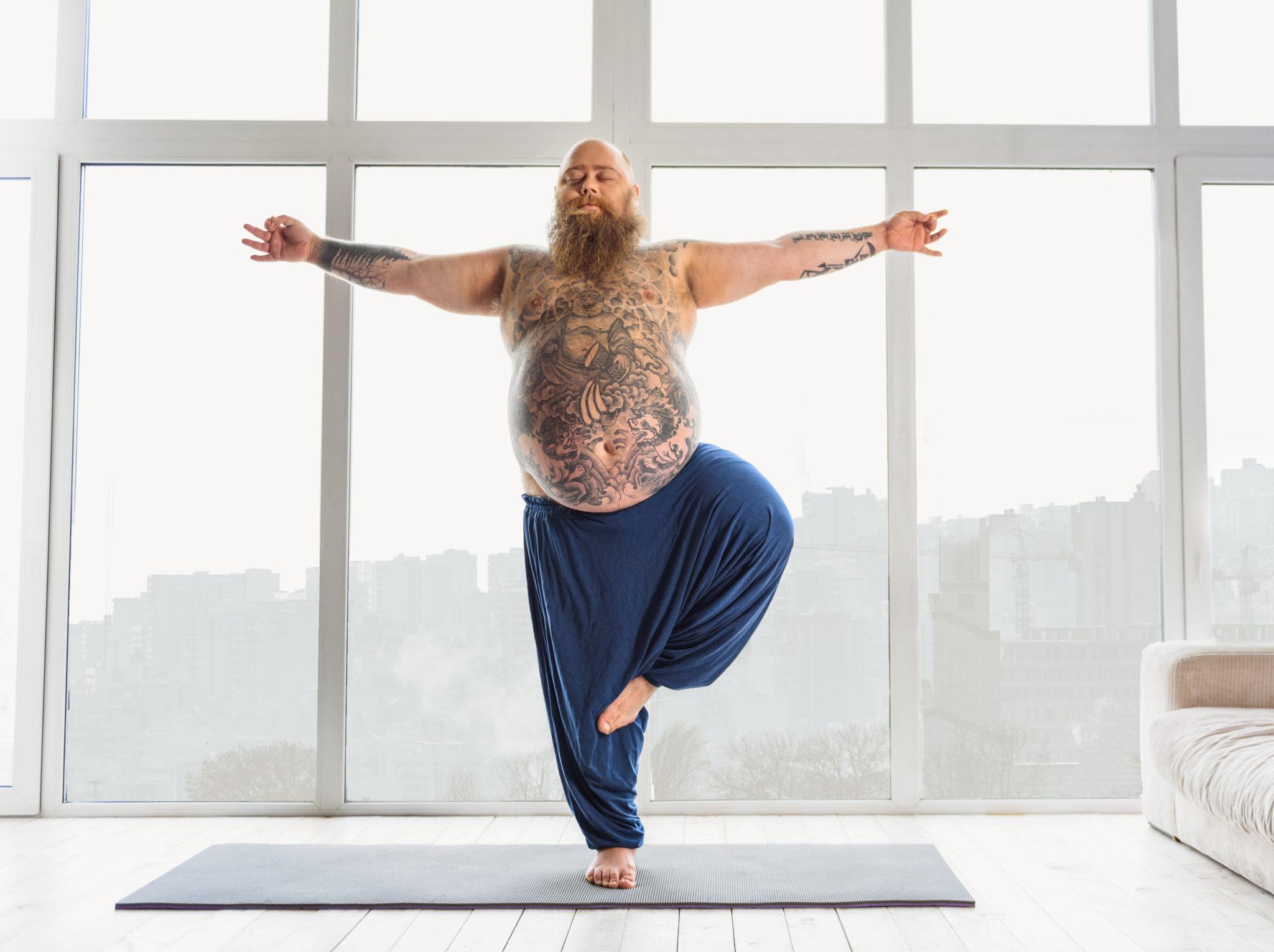 """Man sieht einen Mann mit Bart, Glatze und kugelrundem Bauch in der Yogaposition """"der Baum"""""""