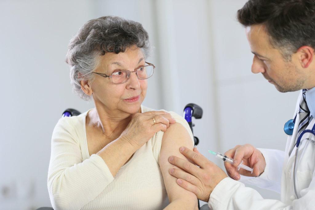 Eine ältere Frau wir von einem Arzt in den Oberarm geimpft.