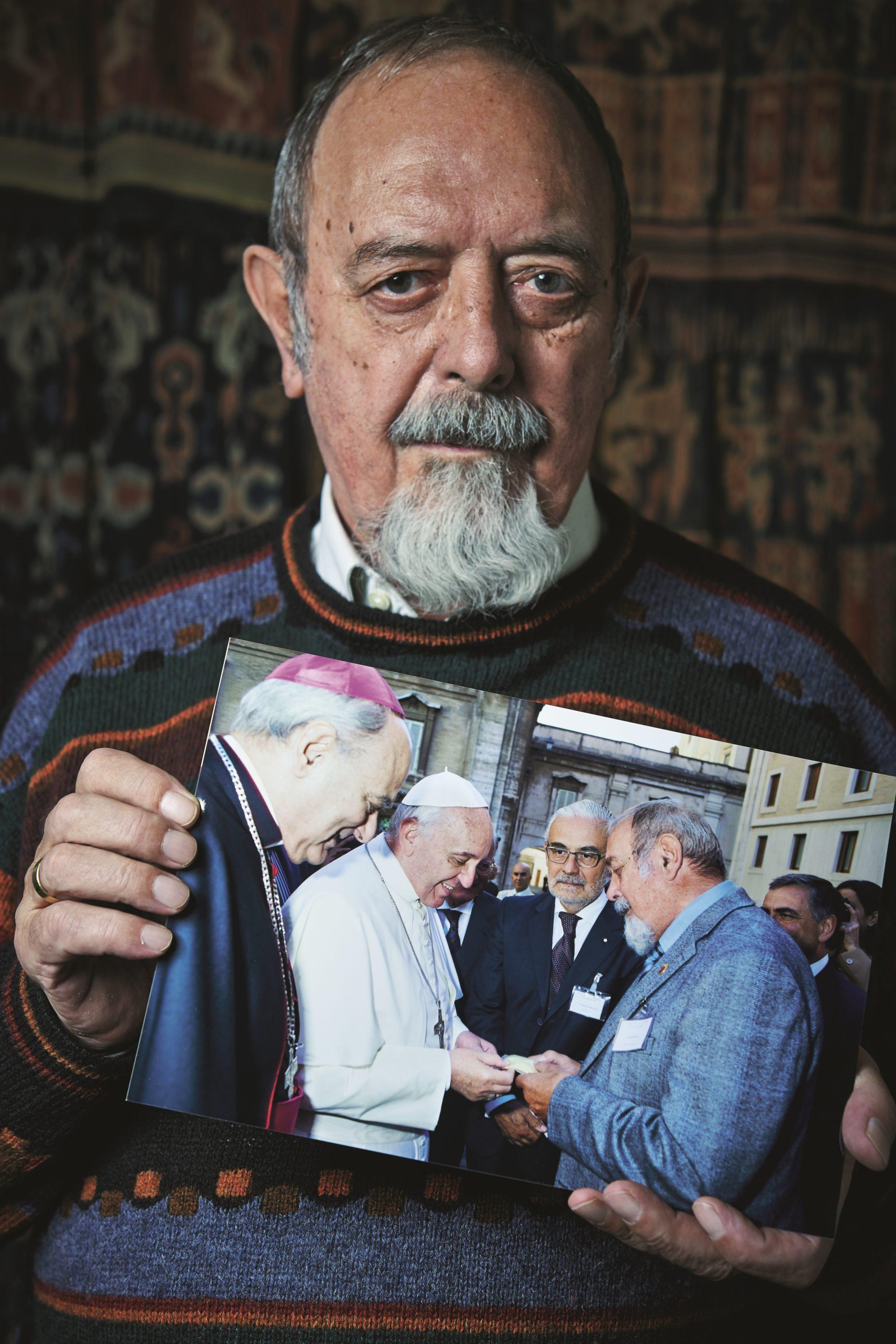 Der Forscher Ingo Potrykus hält ein Foto vor seinen Oberkörper und blickt ernst in die Kamera. Auf dem Foto zu sehen ist Franziskus neben einem Kardinal, der ein Säckchen Reis segnet, dass Ingo Potrykus in den Händen hält.