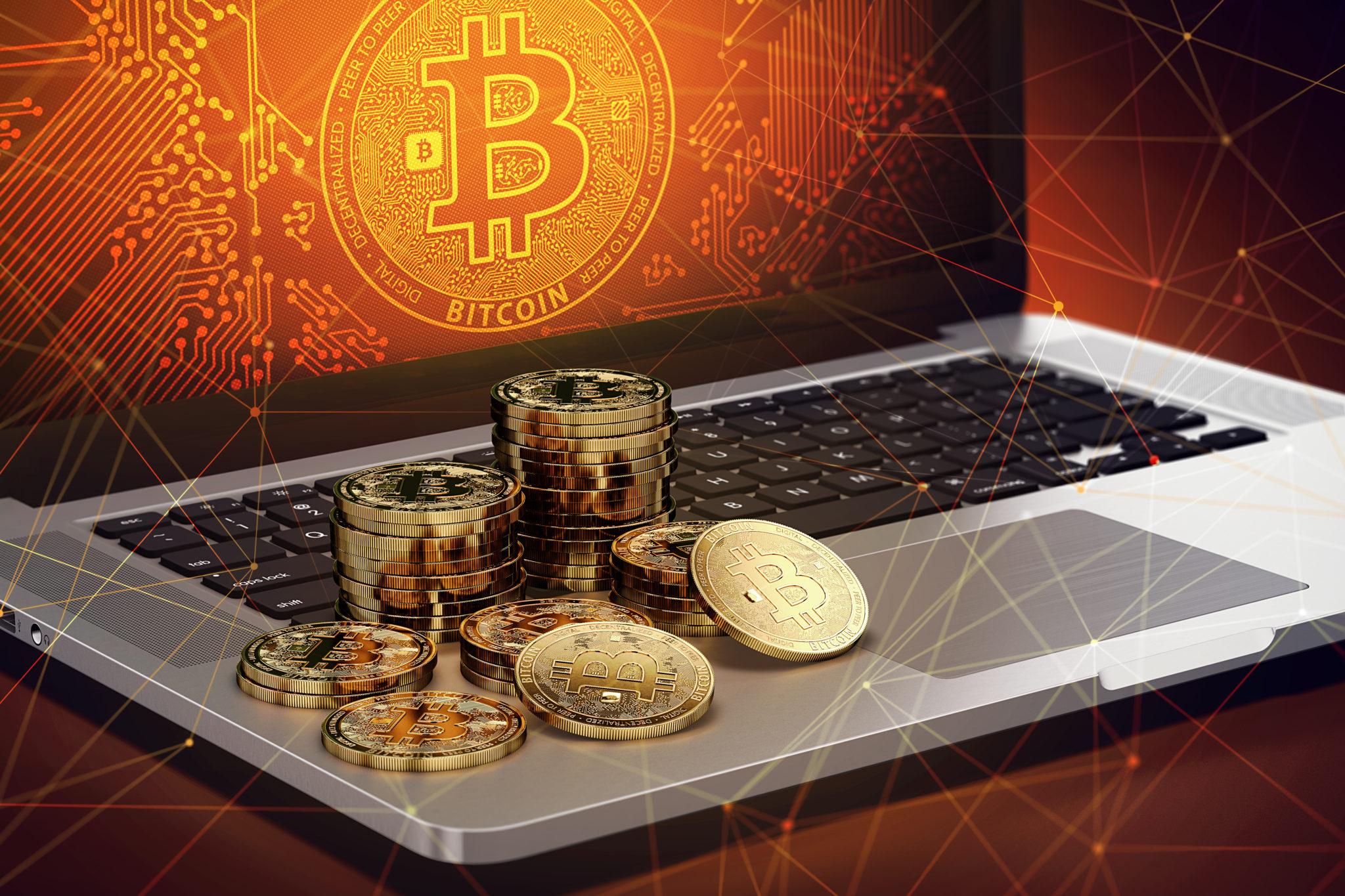 Ein Laptop, auf dem Bitcoin-Taler liegen. Auf dem Bildschirm des Laptops prangt ein rot-gelb leuchtendes Bitcoin-Logo
