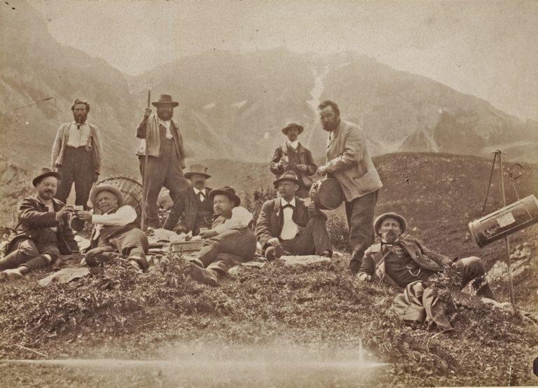Auf dem Schwarz-weiss-Foto sieht man eine Gruppe Botaniker (alles Männer), die gerade auf einer Alpenwiese rasten.