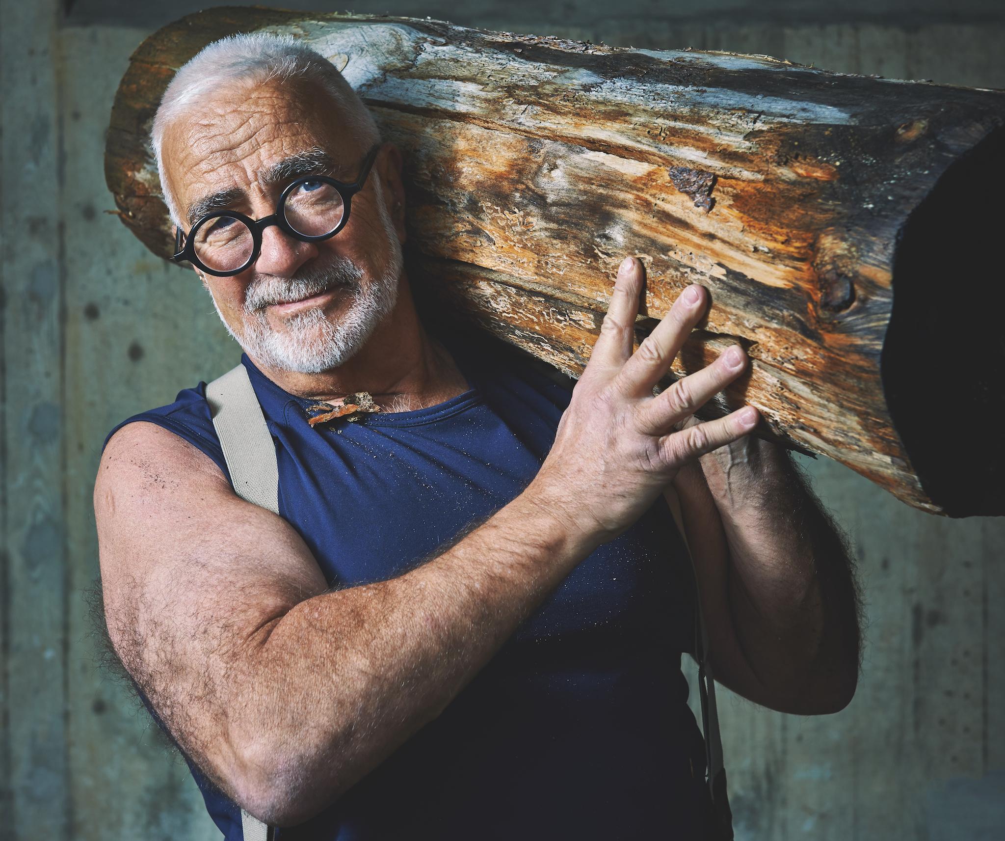 Werner Kieser (grauer Bart mit grauer Millimetterschnitt-Frisur und einer runden, schwarzen Brille hält ein dickes Stück eines Baumstamms auf seiner linker Schulter.