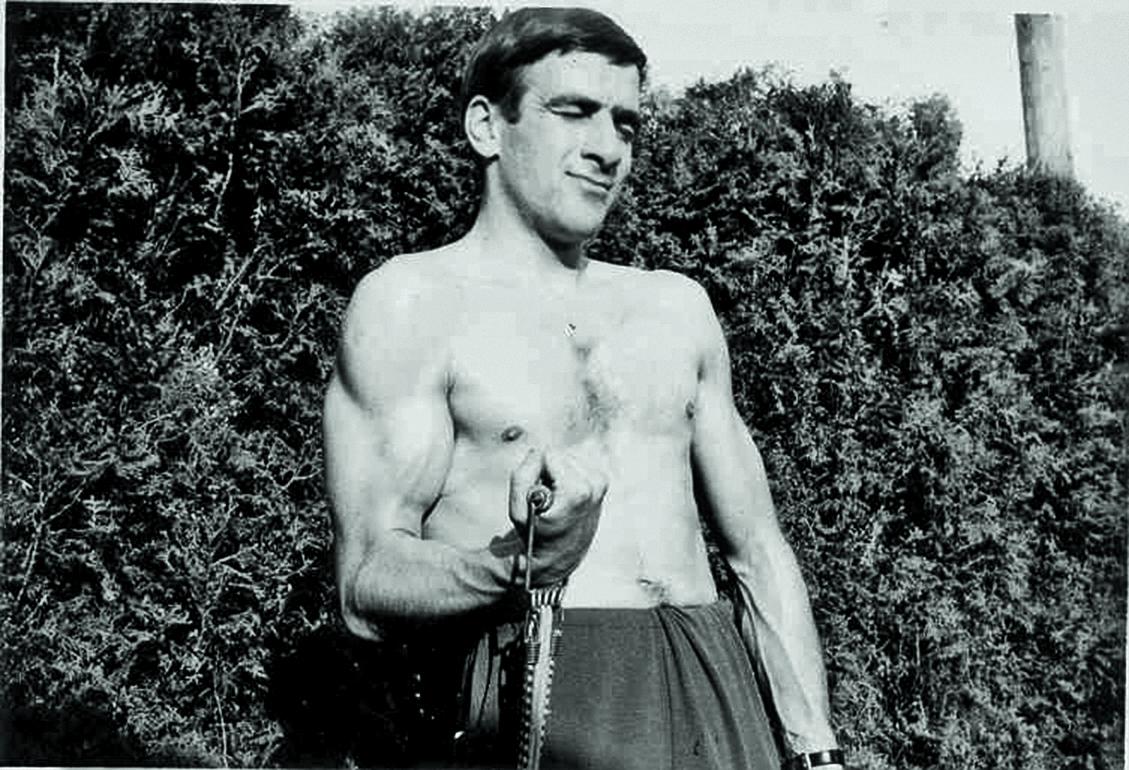 Schwarz-Weiss-Foto eines jungen Werner Kiesers, der mit freiem Oberkörper in einem Garten seine Muskeln trainiert.
