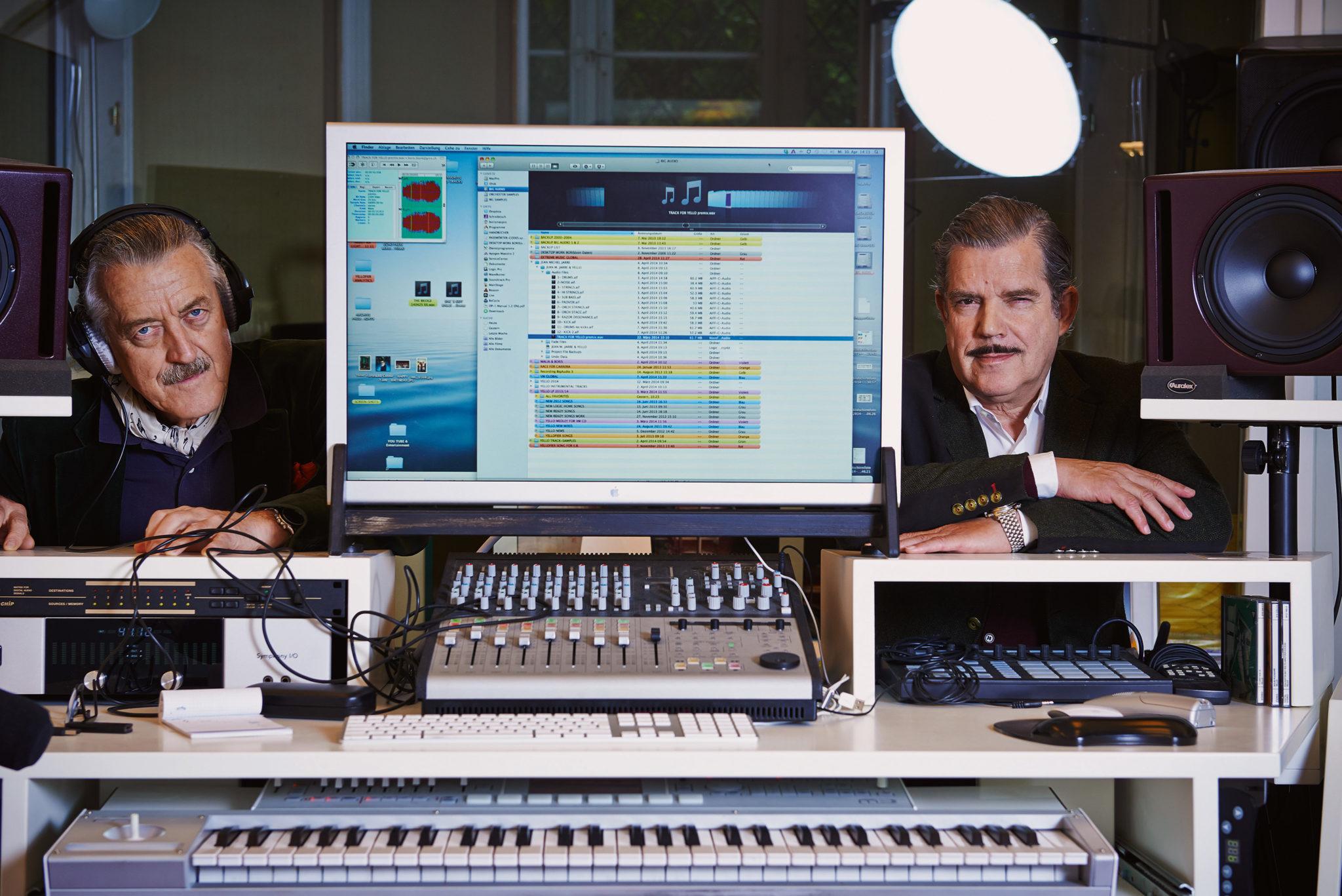 Dieter Meier und Boris Blank posieren in ihrem Tonstudio. Links steht Meier, Blank rechts. in der Mitte ein Mac-Computer.