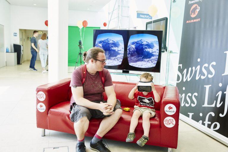 Ein Mann sitzt mit einem Kleinkind auf einem roten Sofa. Das Kind hält eine VR-Brille vor seine Augen.