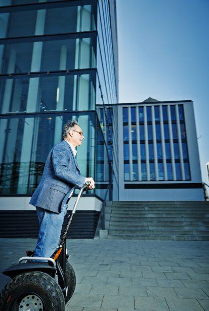 Ein älterer Herr im Anzug fährt links im Bild auf einem Segway nach rechts. Im Hintergrund ist grösserer Glaskomplex.