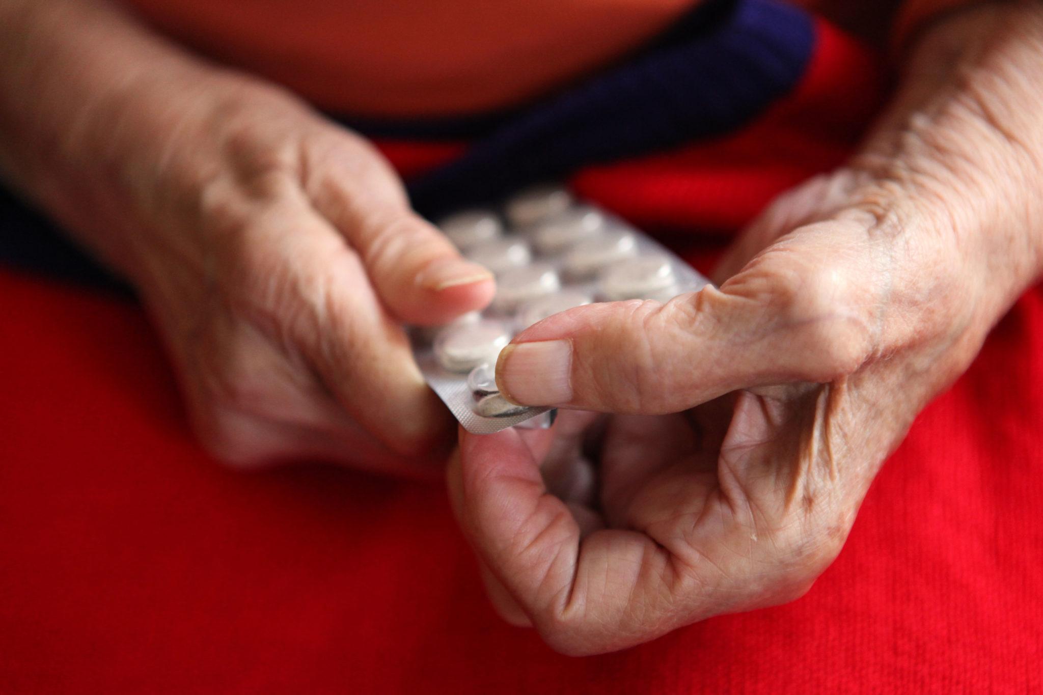 Zwei ältere Hände hantieren mit einer Tablettenpackung.