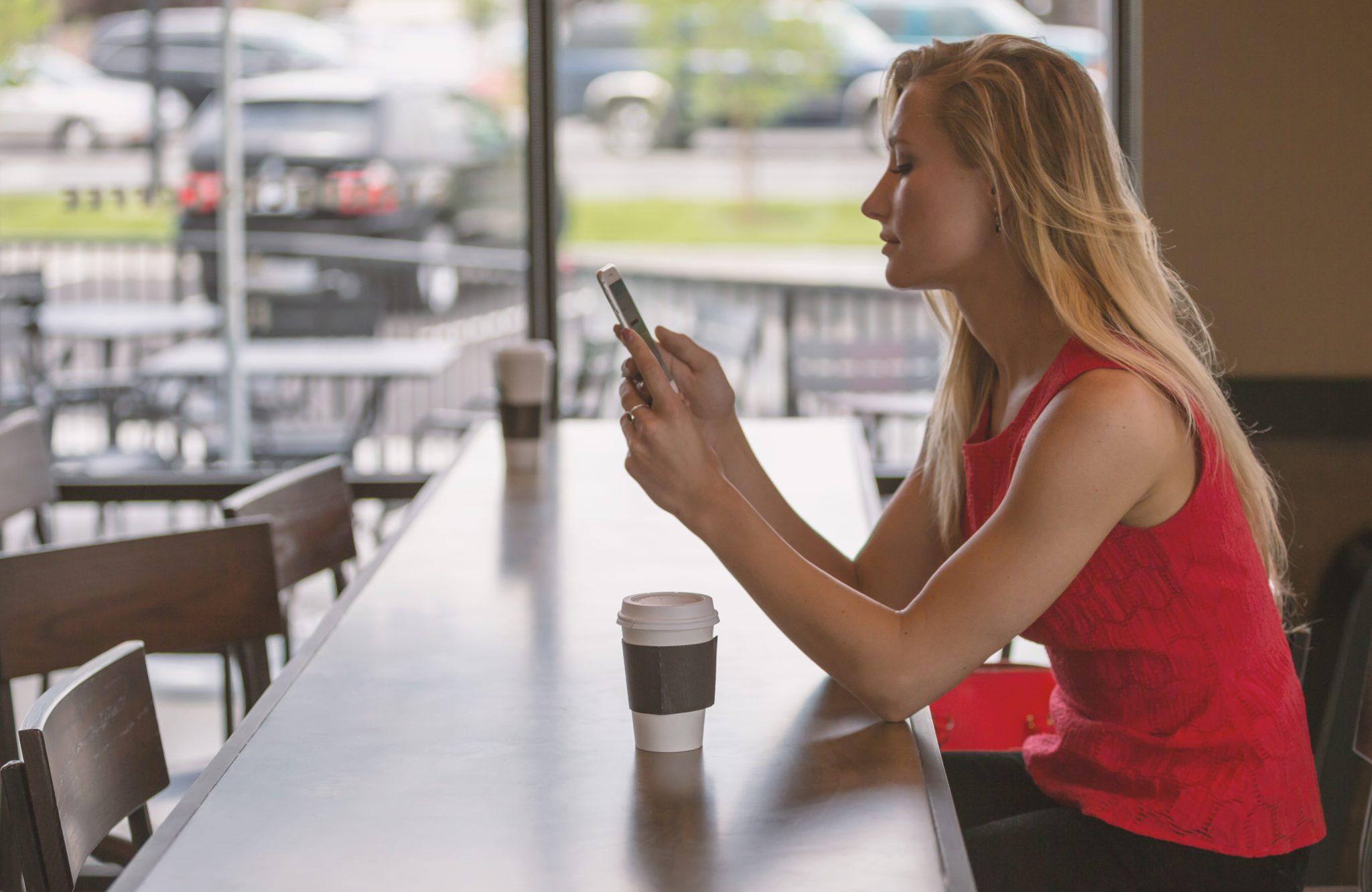 Frau sitzt in einem Kaffee. Vor ihr ein Kaffee, in den Händen hält sie ein Smartphone.
