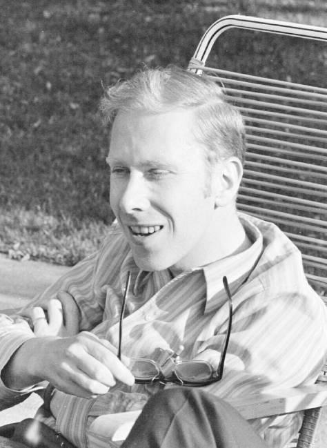 Eine Schwarz/Weiss-Fotografie eines junges Mannes, der in einem Liegestuhl lacht. In den Händen hält er eine Brille