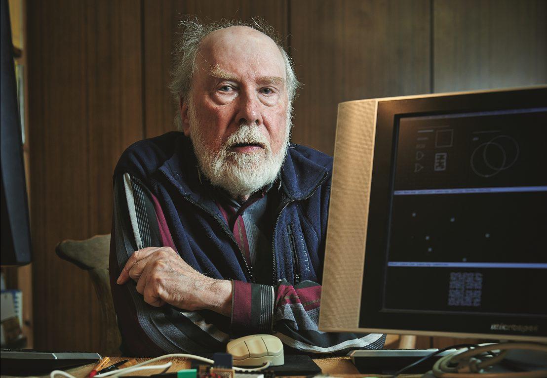 Ein älterer Herr mit Halbglatze und weissem Vollbart sitzt an einem Tisch. Vor ihm der Bildschirm eines alten Computers, auf dem Kreise, Punkte und geometrische Figuren zu sehen sind.