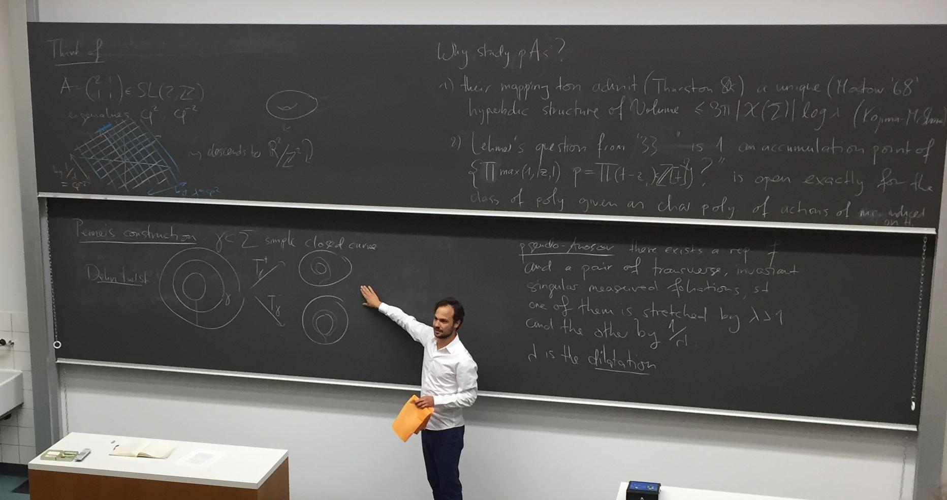 Ein jüngerer Herr in weissem Hemd steht vor einer grossen Wandtafel in einem Hörsaal. Er zeigt auf mathematische Formeln zu seiner Rechten. Links stehen ein paar englische Sätze.