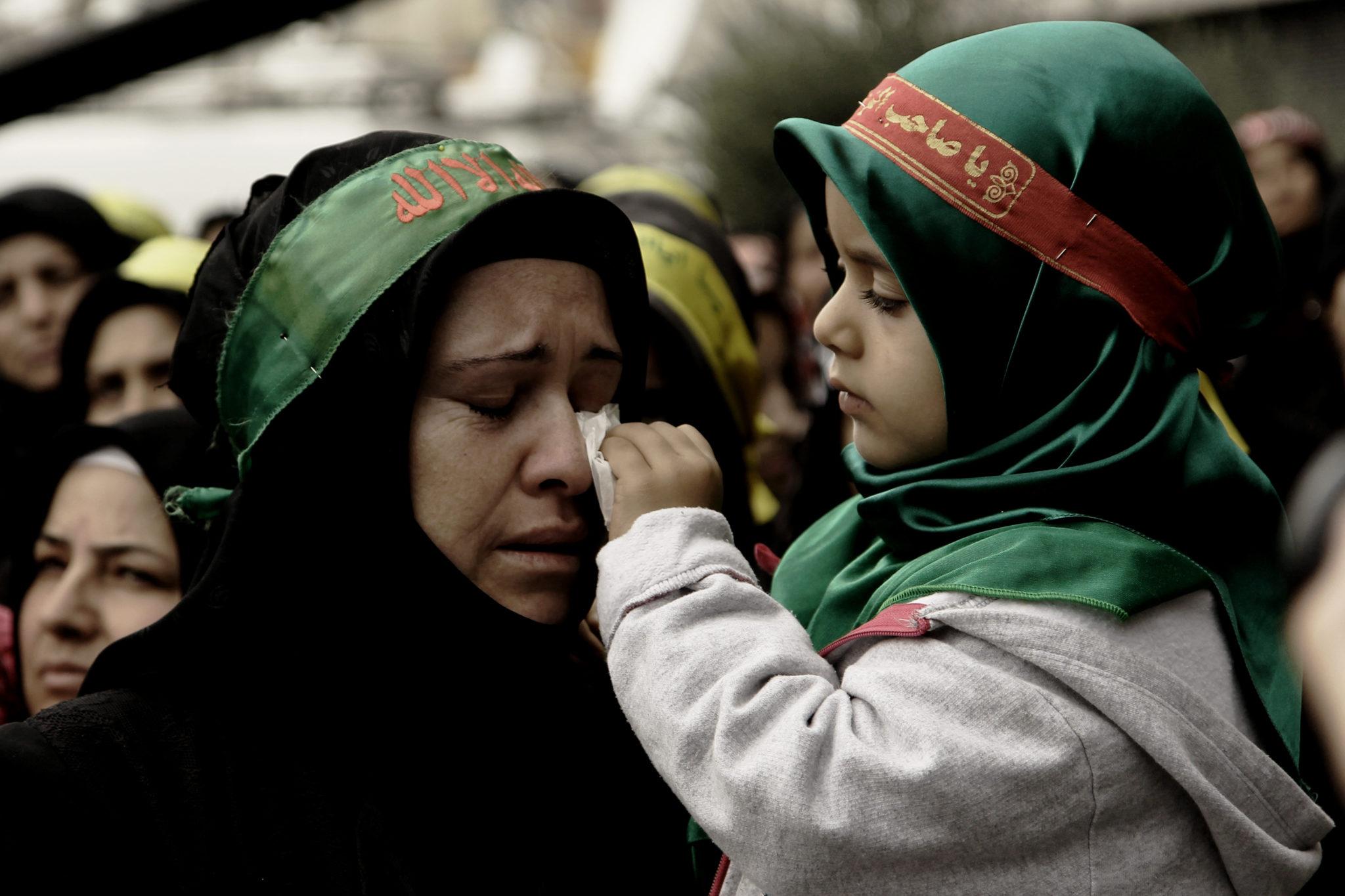 Eine muslimische Frau und ihre Tochter sind in Not. Die Mutter weint, das Kind auf ihrem Arm wischt ihr mit einem Tuch die Tränen weg.