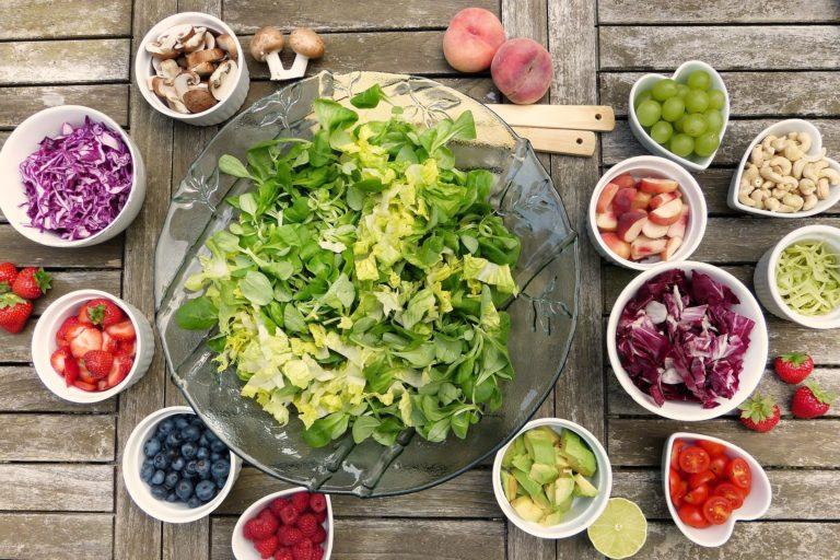 Auf einem Holztisch steht mittig eine grosse Glasschale mit Salat. Darum herum viele kleinere Schälchen mit Beeren, Trauben, Tomaten, Erdbeeren und Pilzen.