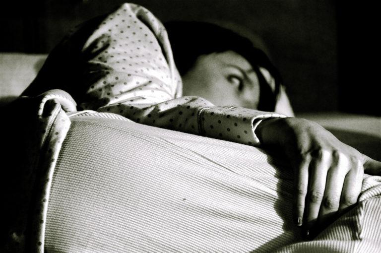 Schwarzweiss-Foto einer Frau, die wach im Bett liegt.