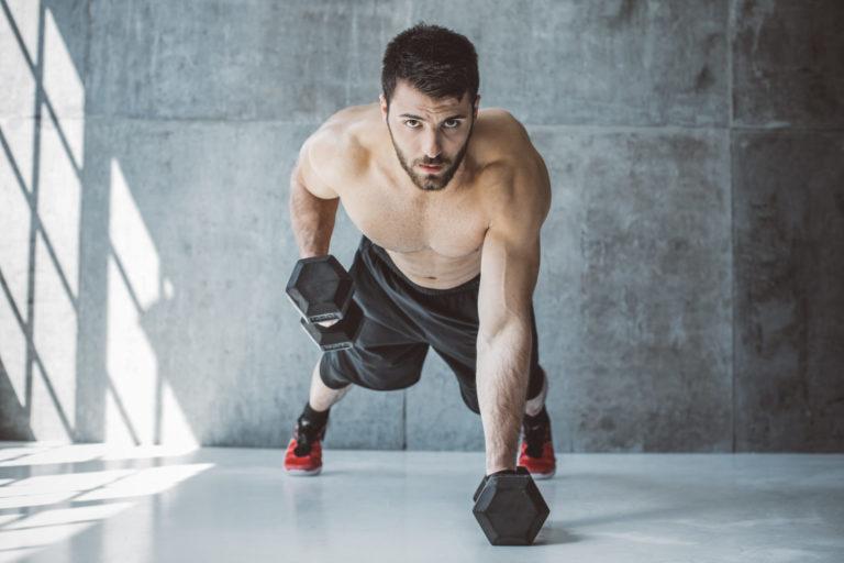Ein Mann mit freiem Oberkörper trainiert mit Hanteln.