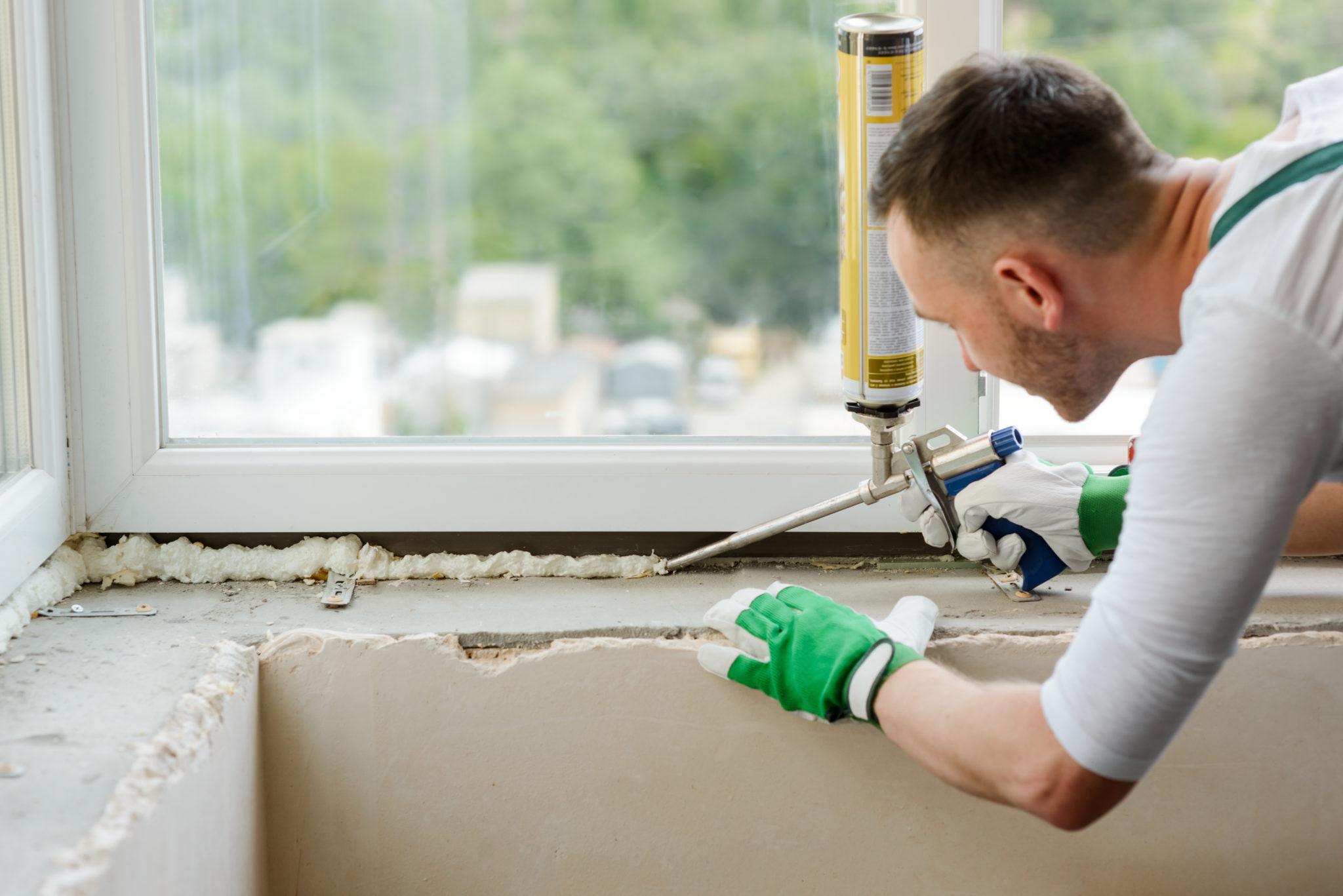 Ein Arbeiter dichtet ein Fenster mit Polyurethan-Schaum ab.