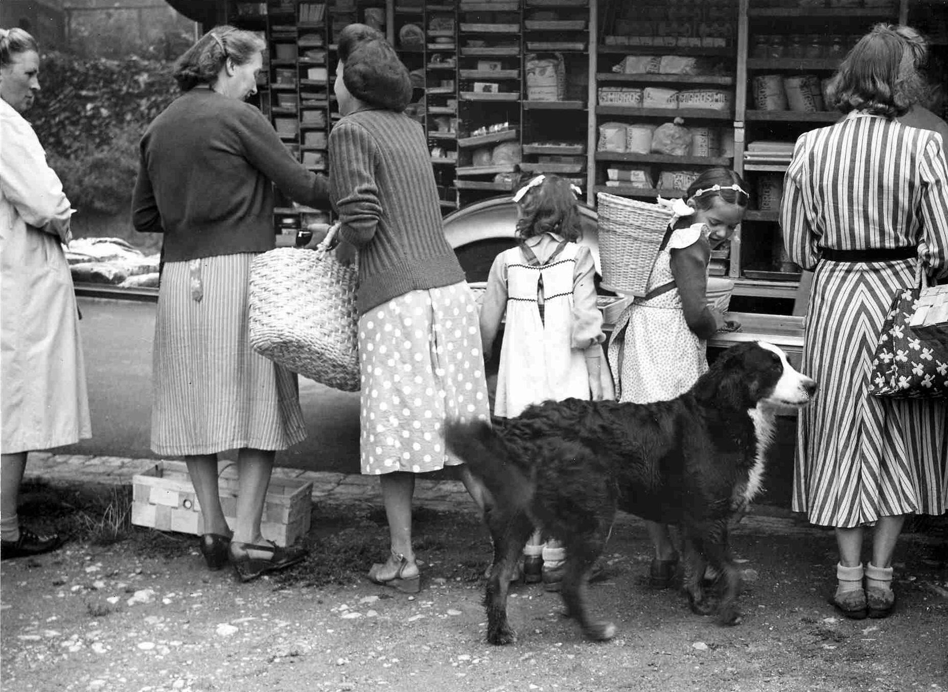 Schwarz-Weiss-Foto. Vier Frauen, zwei junge Mädchen und ein Hund stehen vor einer Warenauslage im Freien.