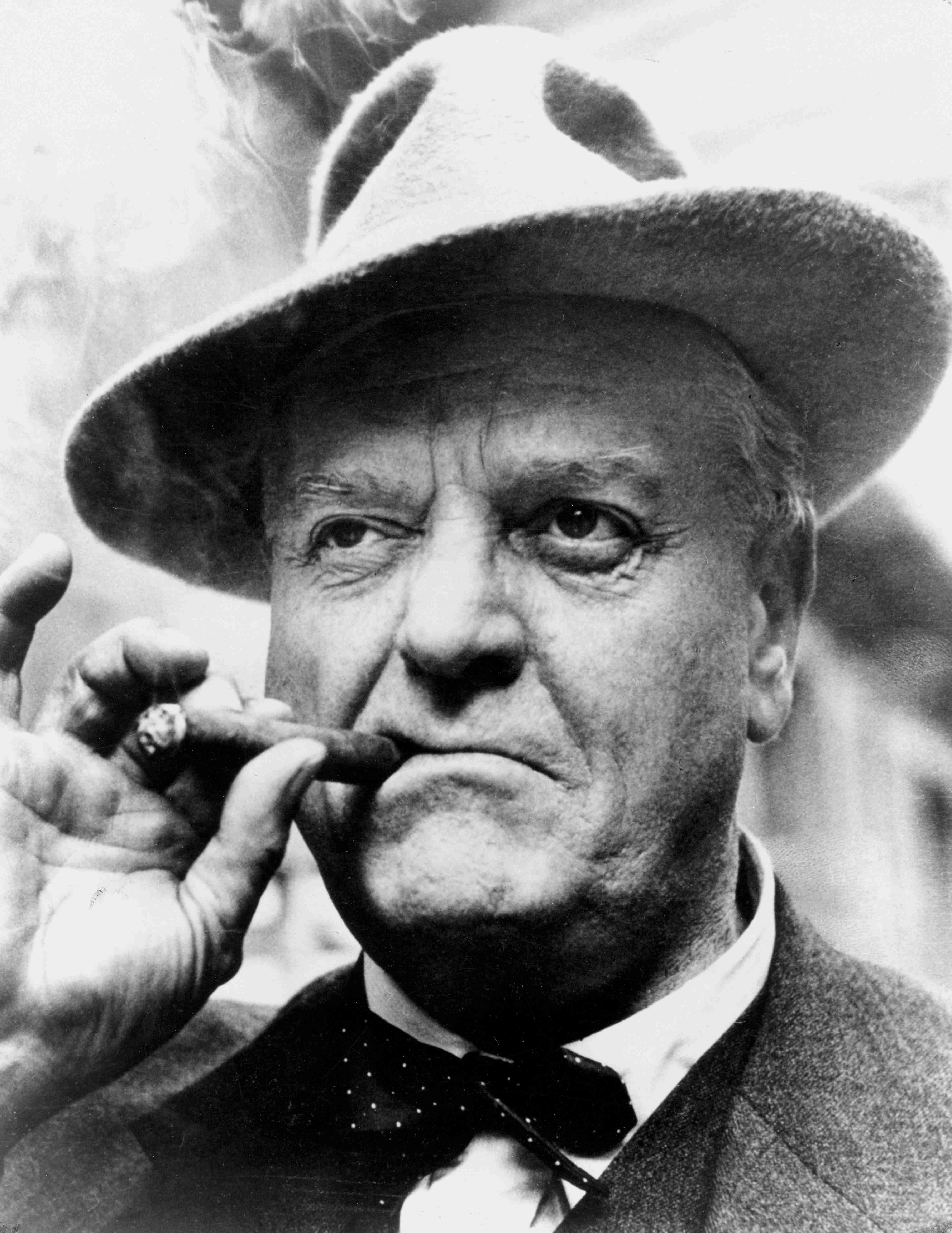 Schwarz-Weiss-Foto. Älterer, leicht übergewichtiger Herr mit schrägem Hut und Anzug. Im Mundwinkel hält er zwischen Daumen und Zeigefinger eine brennende Zigarre.