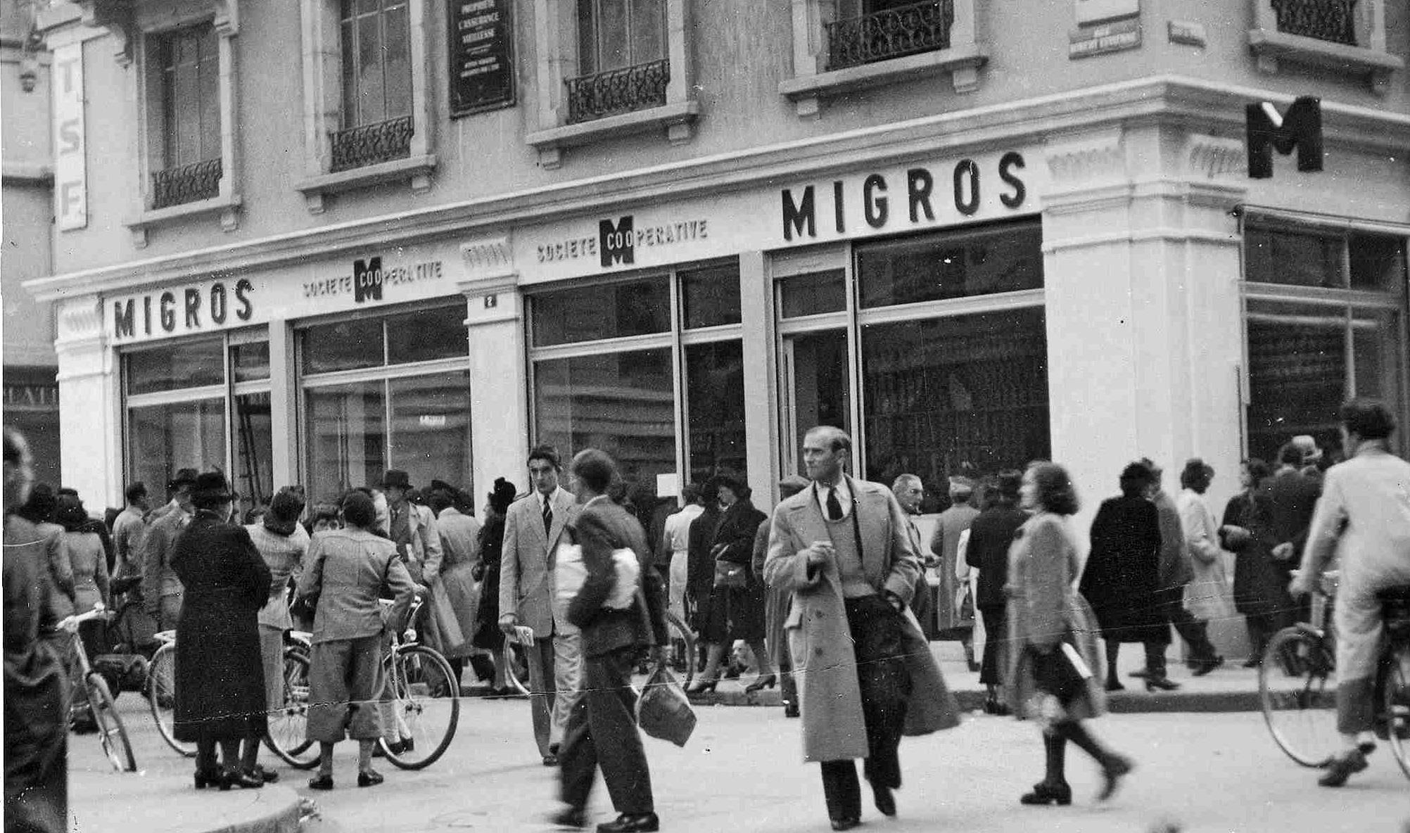 Schwarz-Weiss-Foto. Belebte Strasse, im Hintergrund eine Migros-Filiale.