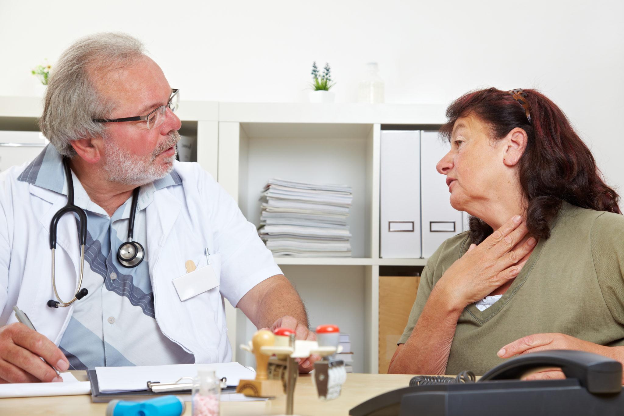 Seniorin mit Halsschmerzen beim Arzt in der Praxis