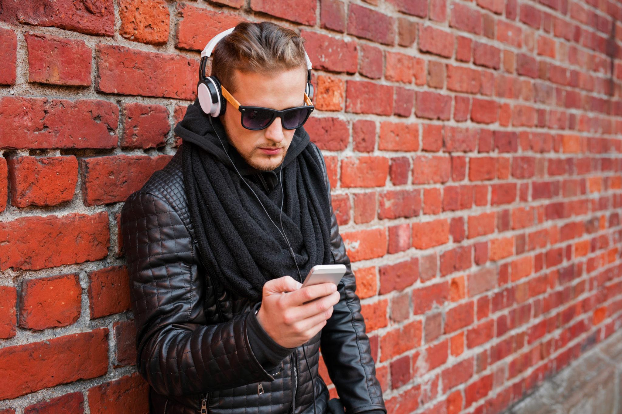 Ein junger Mann hört mit Kopfhörern von seinem Handy aus Musik.