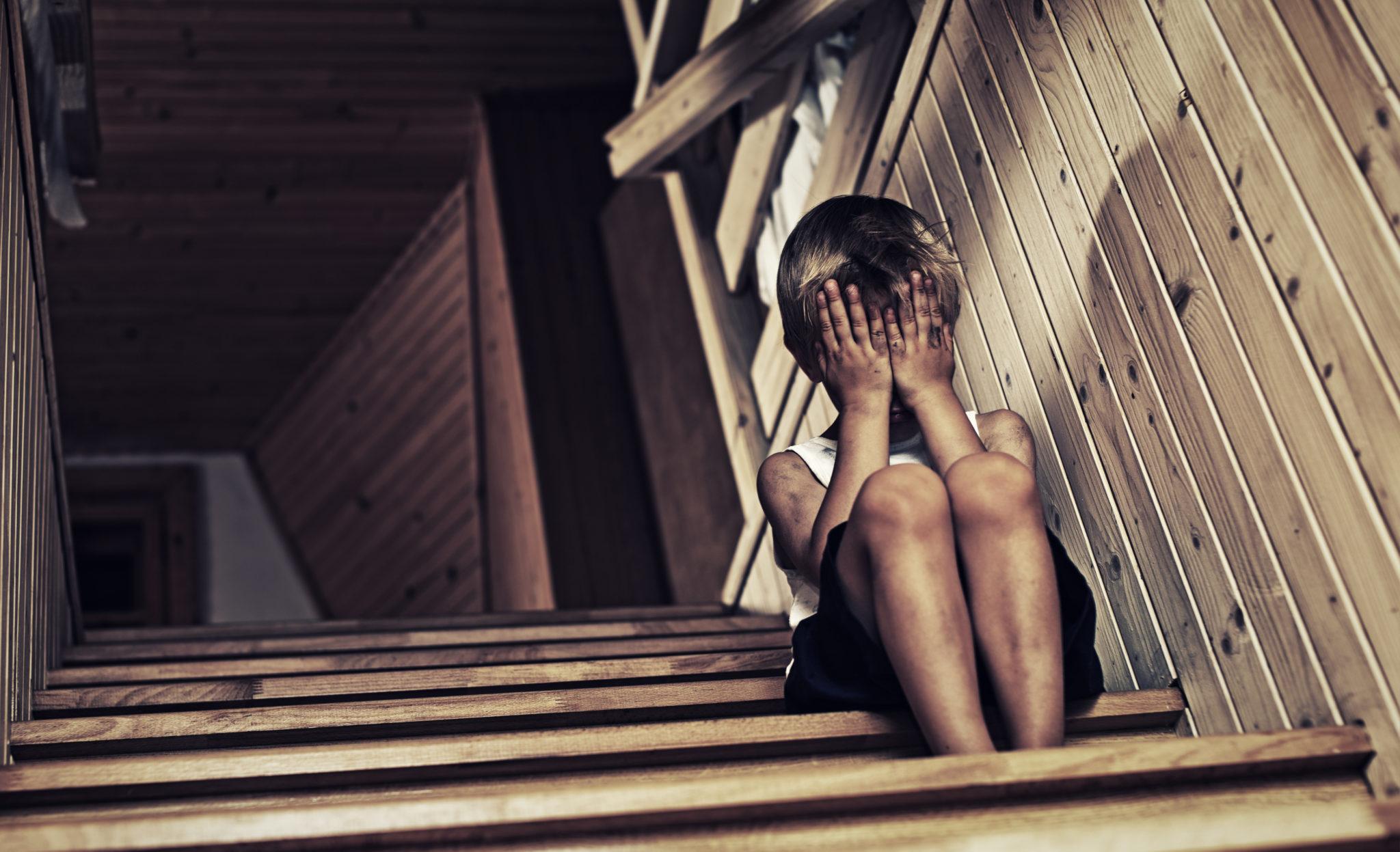 Kleiner Junge, weinend auf einer Treppe sitzend.