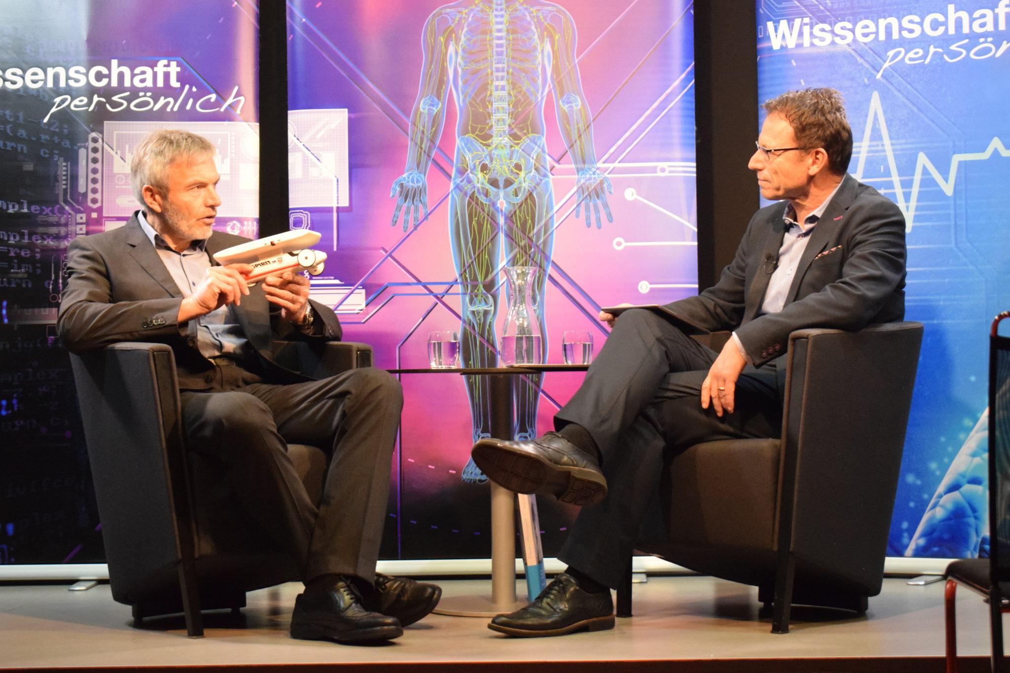 Bernhard Gerster (links) auf der Bühne von «Wissenschaft persönlich»: Am Modell des Pionier-Solarmobils «Spirit of Biel» erklärt er, wie dessen Sonnenpanels funktionieren.