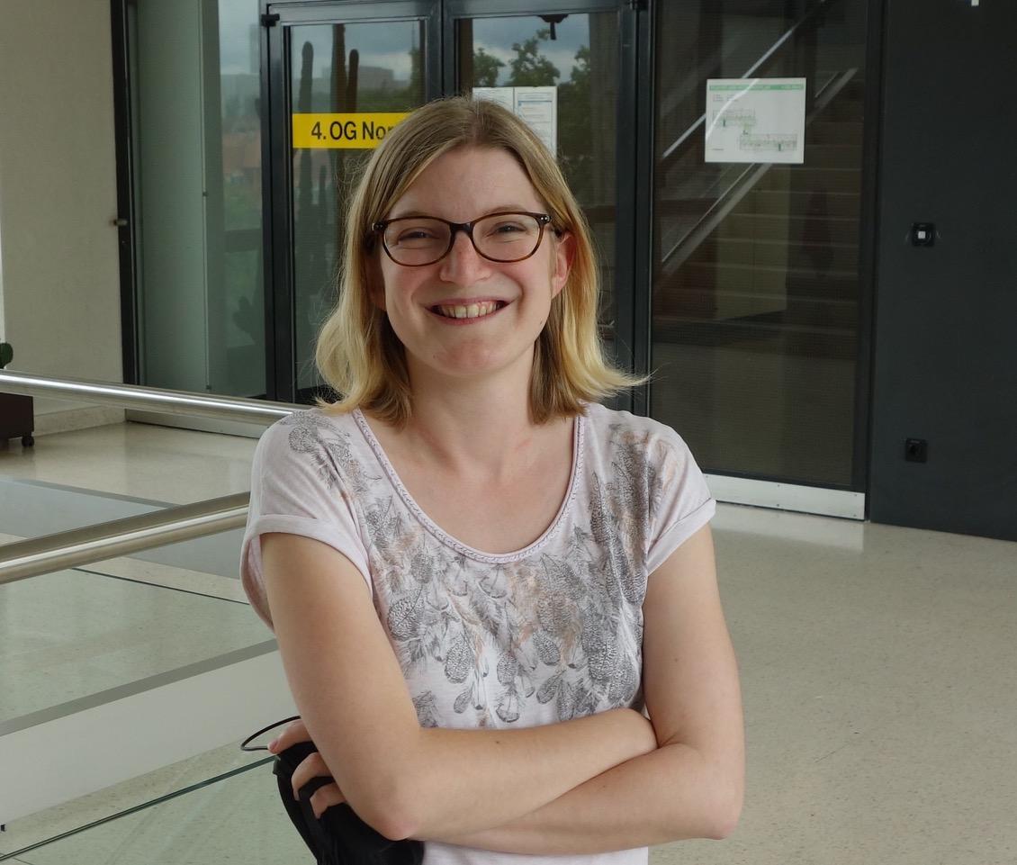 Junge blonde Frau mit Brille lächelt mit verschränkten Armen in die Kamera