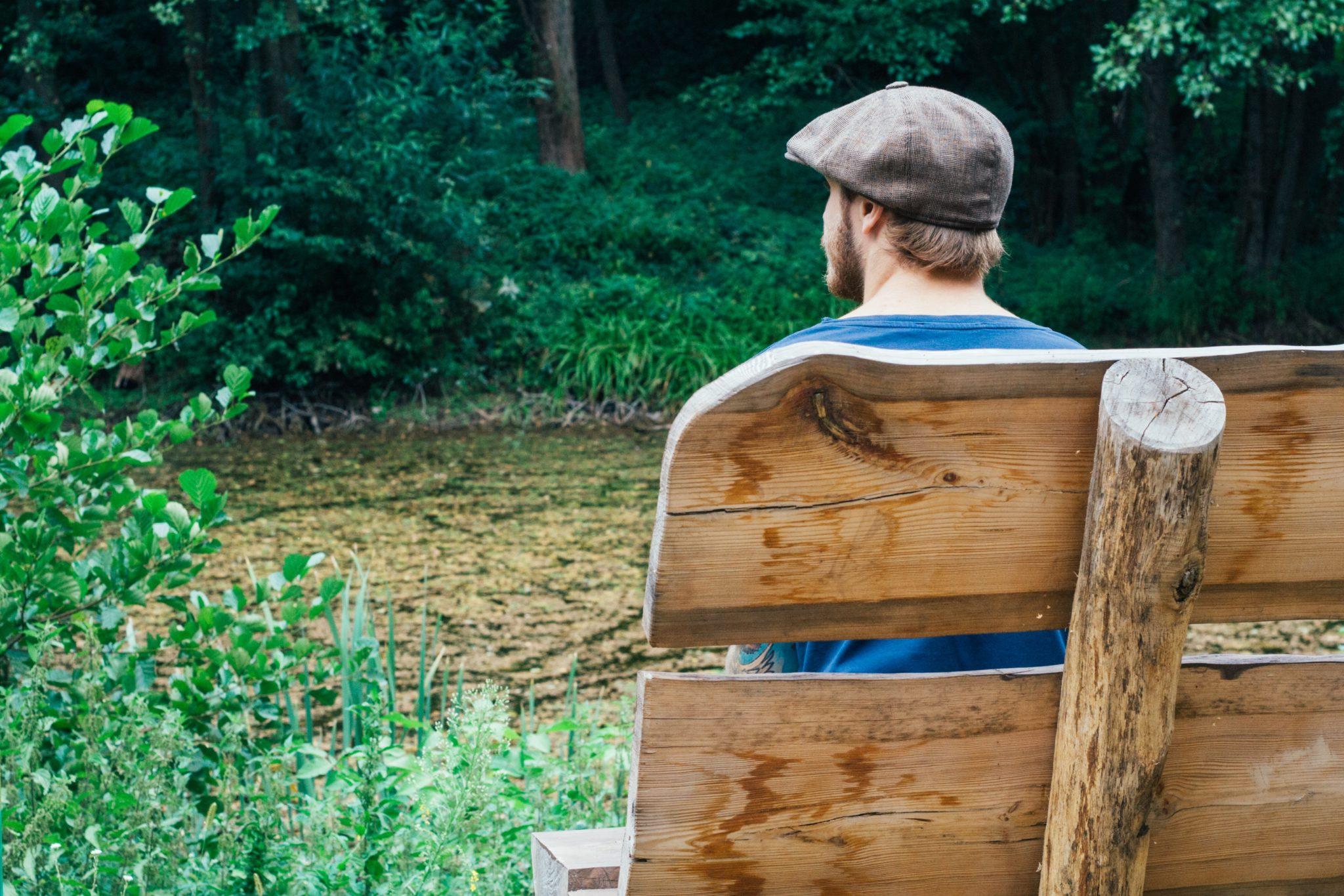 Mann sitzt auf einer Parkbank im Grünen.