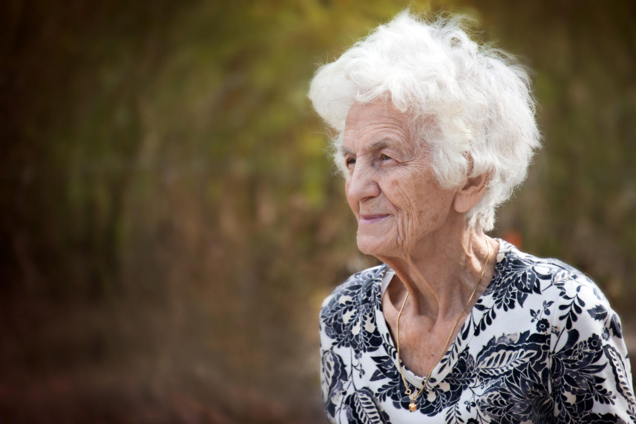 Alte Frau schaut sinnierend in die Ferne.