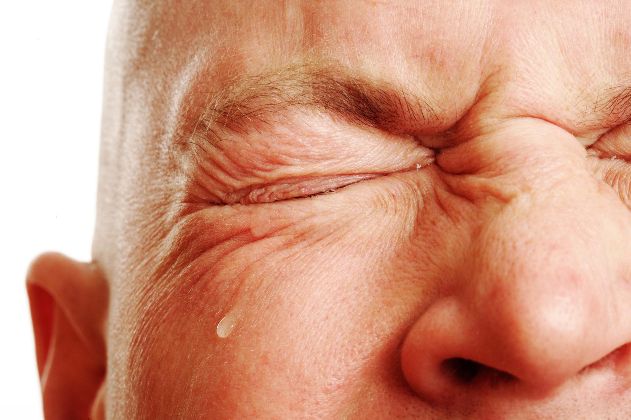 Ein Mann drückt schmerzverzerrt seine Augen zu. Eine Träne kommt aus dem rechten Auge.