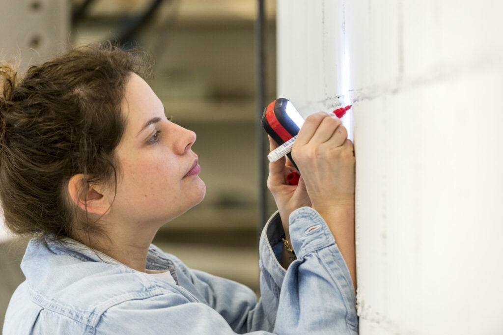Eine Bauingenieurin der Hochschule Luzern überprüft die Mauer nach jedem Durchgang genauestens, um auch kleinste Risse zu entdecken.
