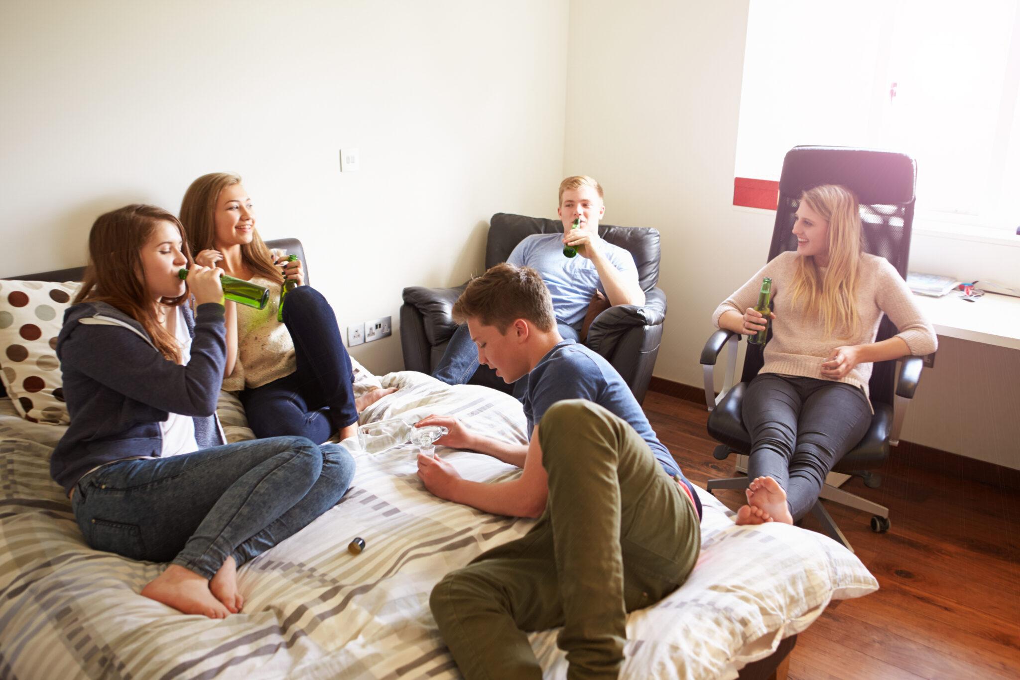 Eine Gruppe Jugendliche trinkt Alkohol im Zimmert