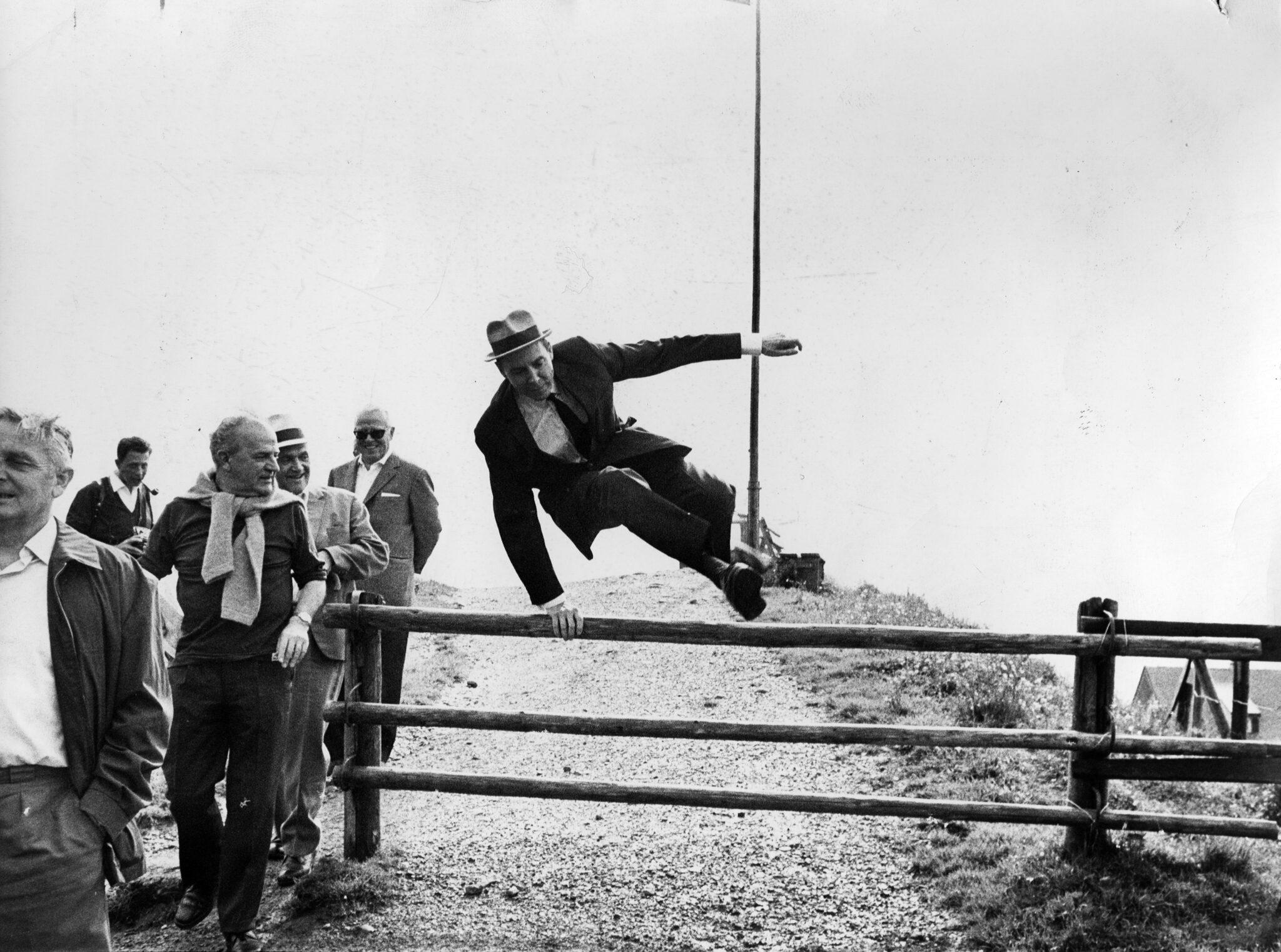 Mann hüpft über Zaun