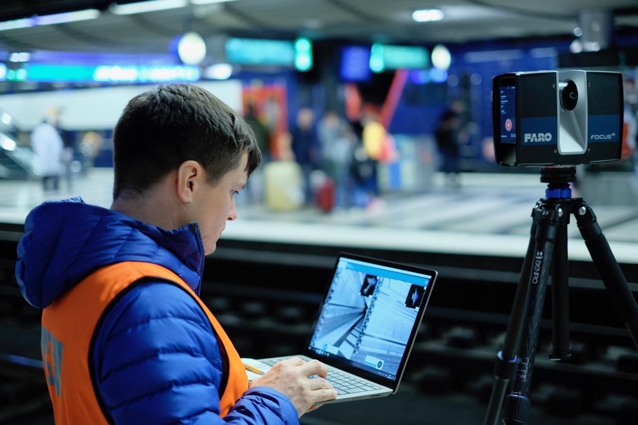 Mann mit Laptop und Messgerät am Bahngleis