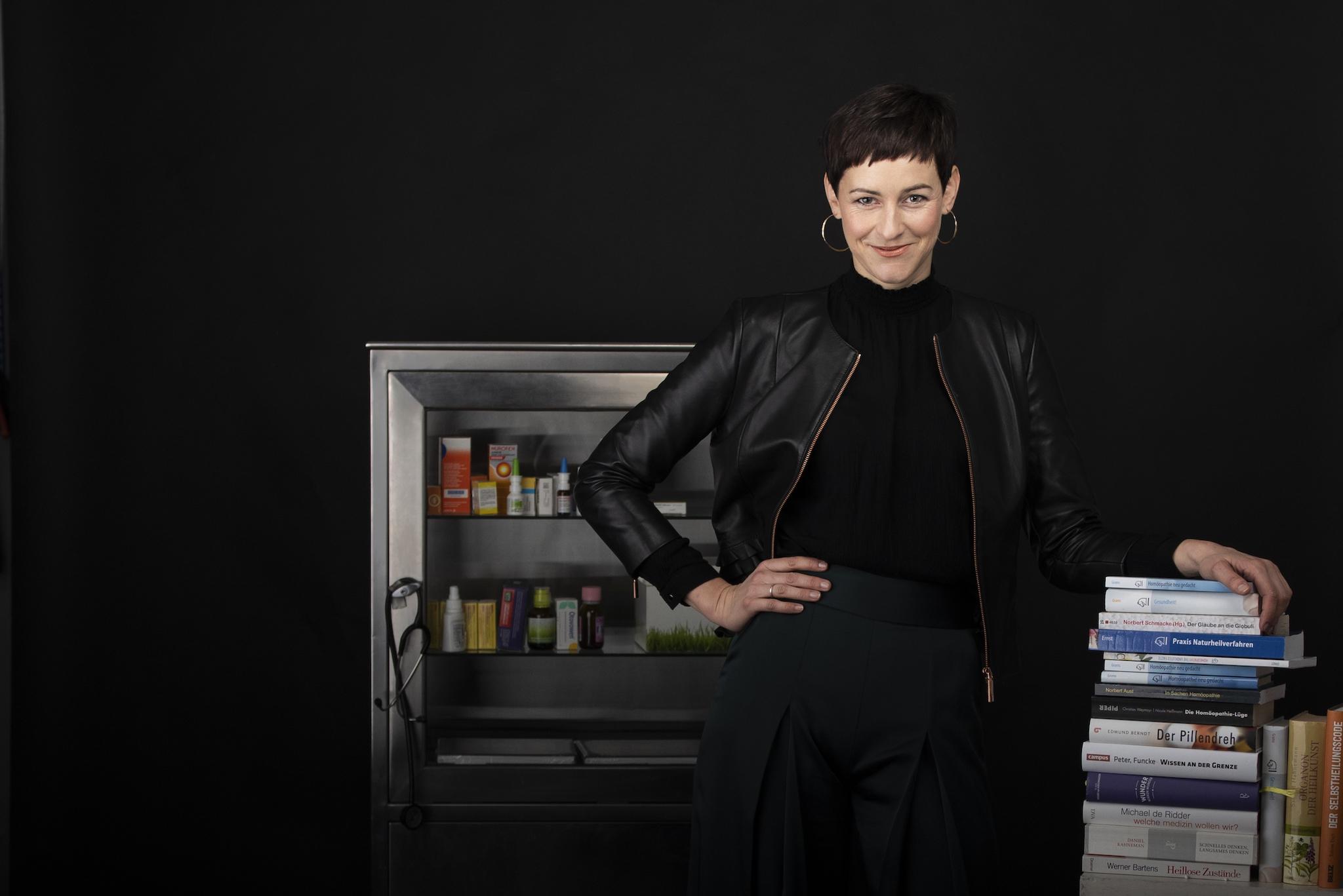 Homöopathiekritikerin Natalie Grams neben Büchern und vor Mediamentenschrank