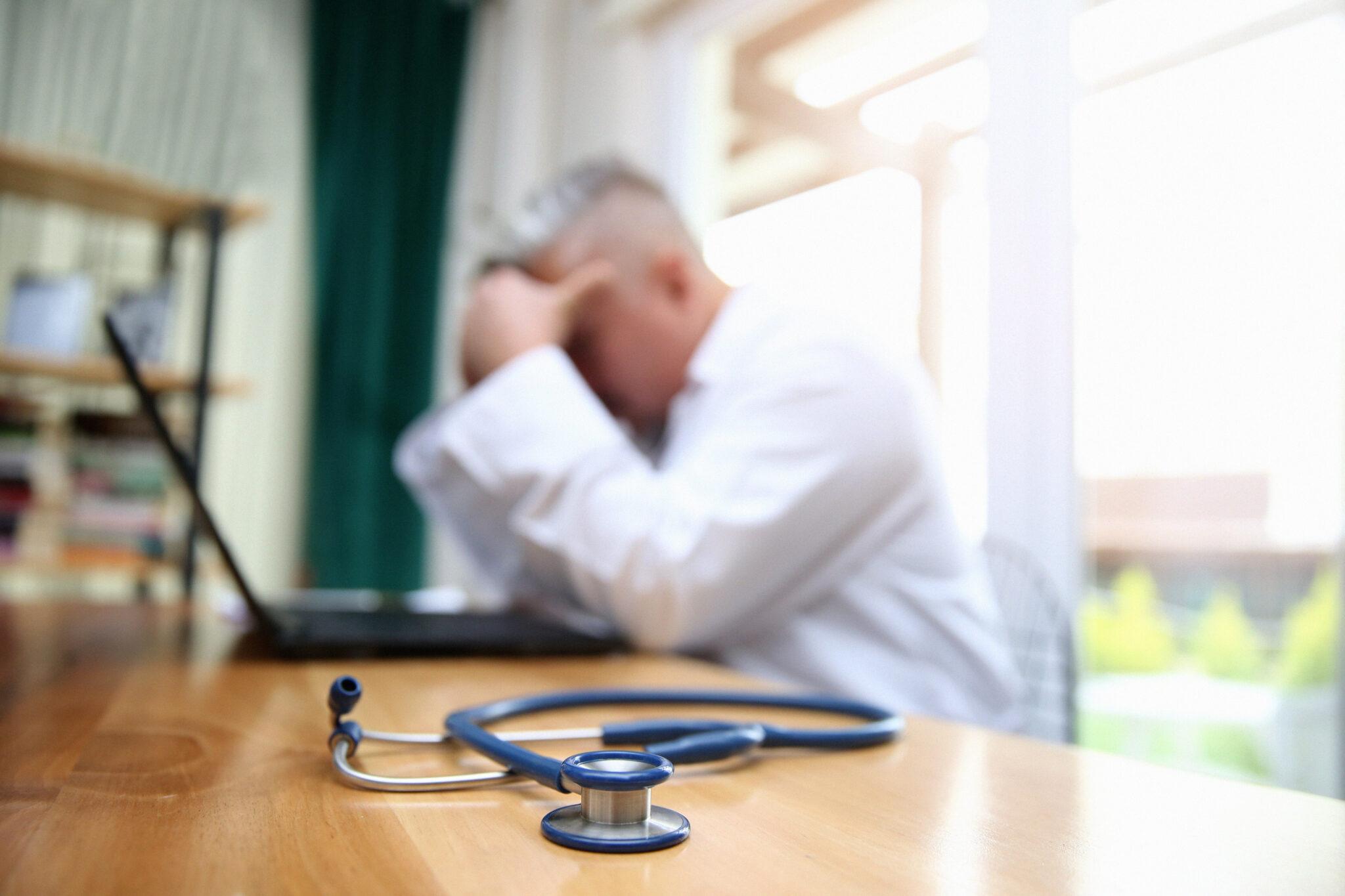 Verzweifelter Arzt, der sich auf dem Tisch aufstützt