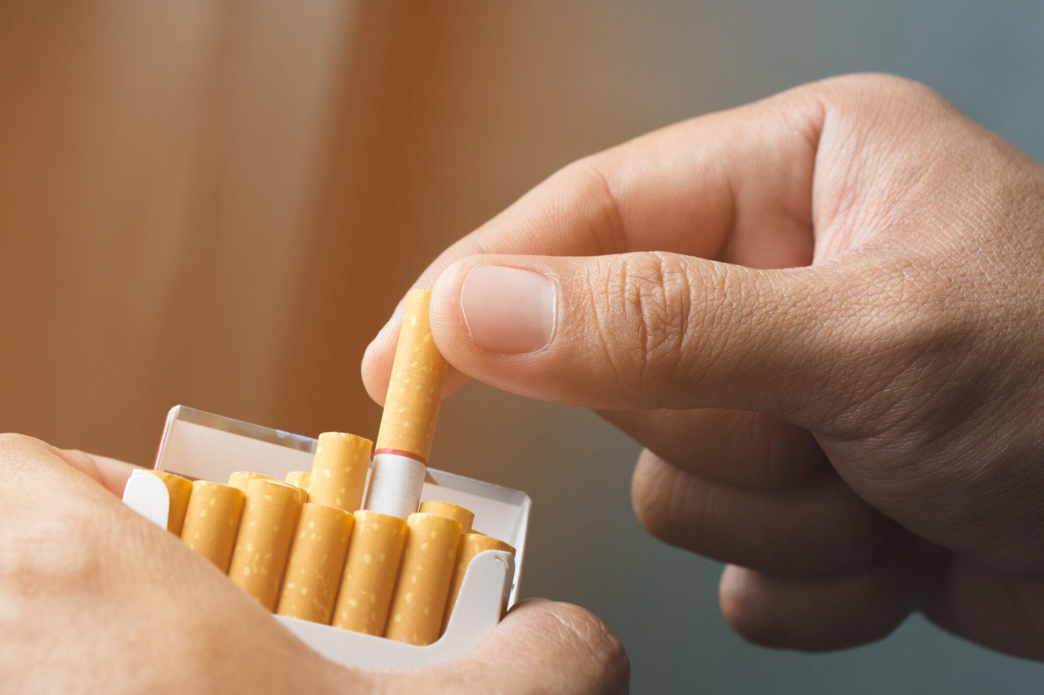 Hand greift zur Zigarettenschachtel