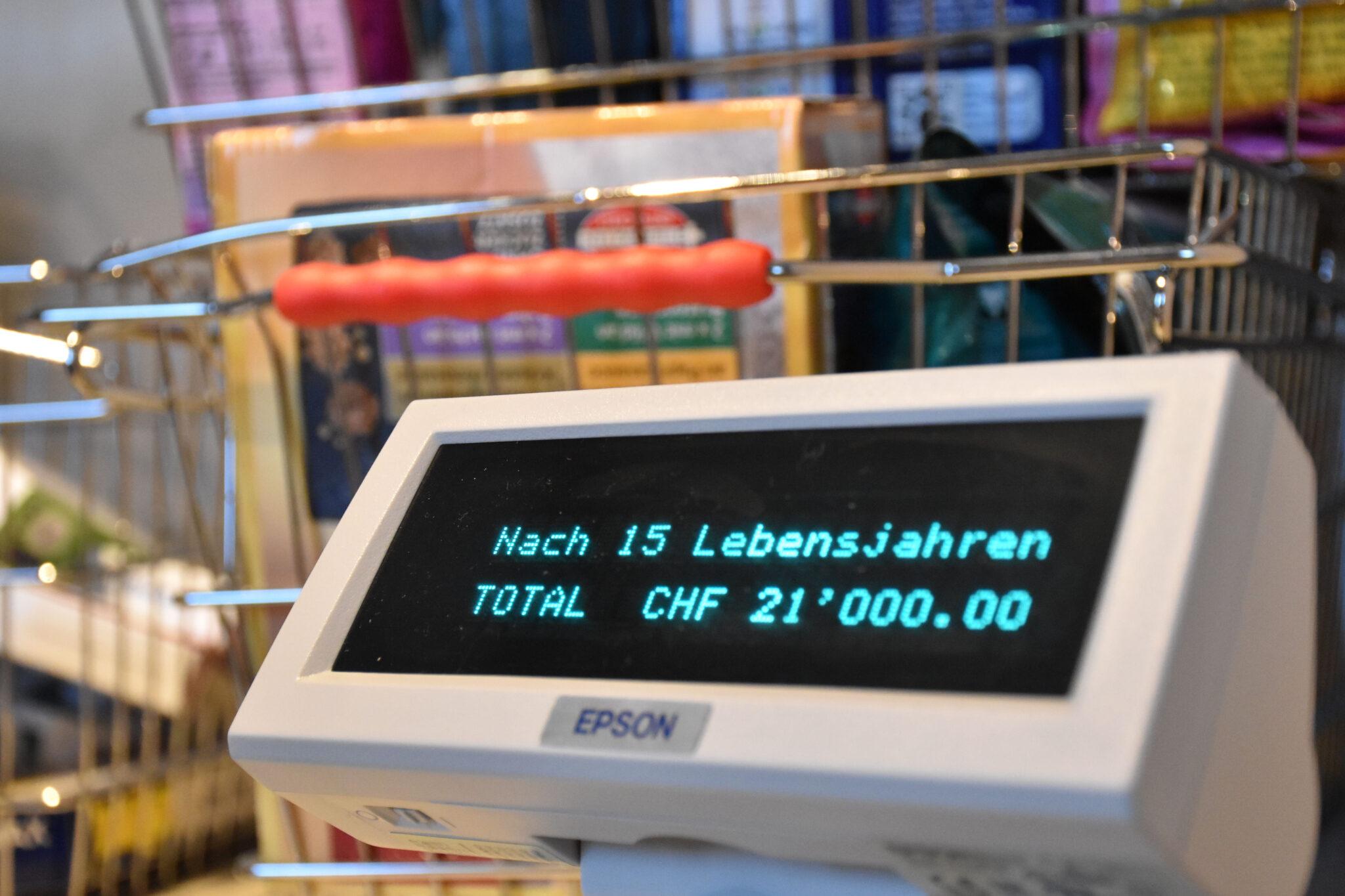 """Kasse im Supermarkt mit der Aufschrift """"Nach 15. Lebensjahren TOTAL CHF 21'000.00"""""""