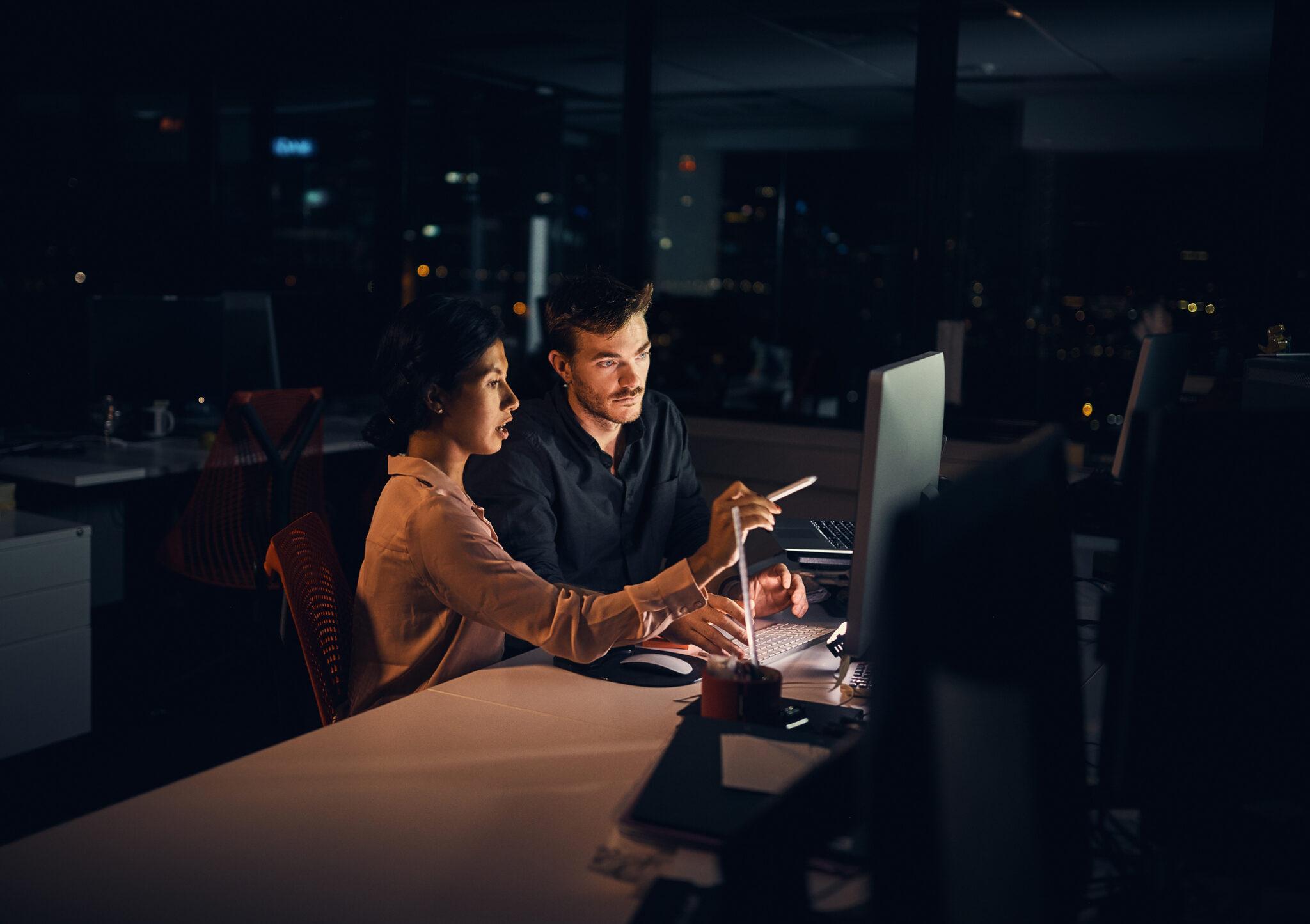 Zwei Menschen sitzen spät abends / nachts im Büro