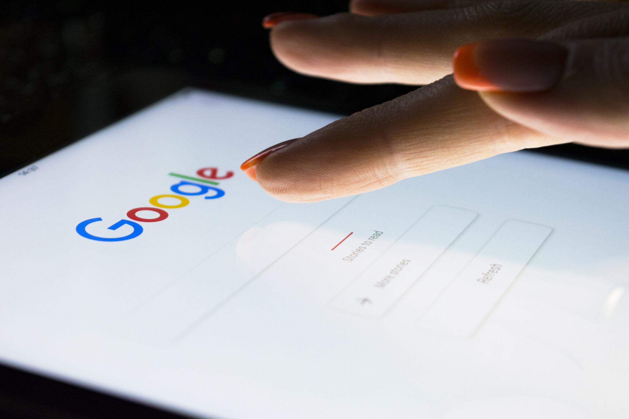 Finger auf iPad tippt etwas in die Google-Suche ein