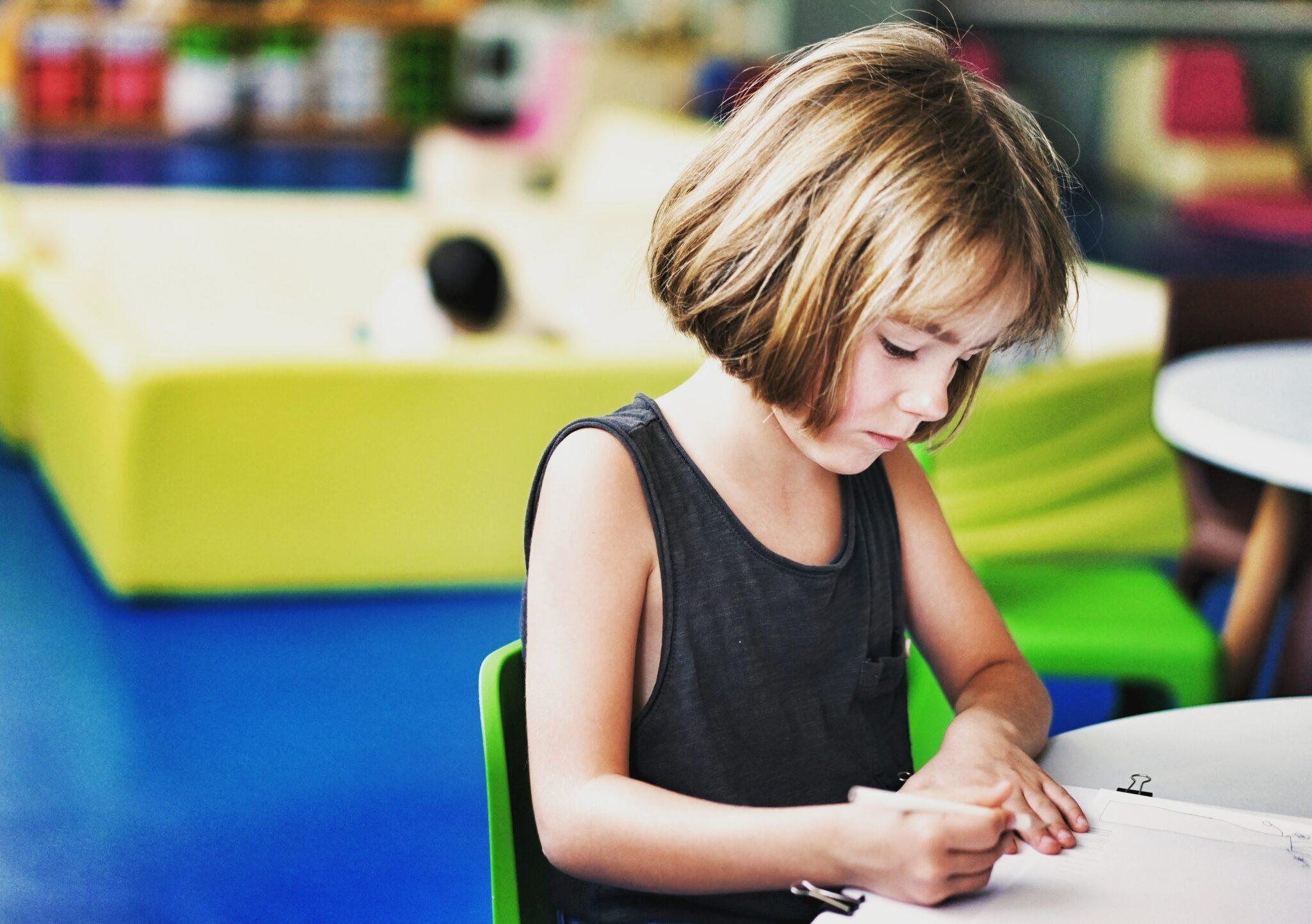 Ein Mädchen sitzt an einem Tisch und schreibt etwas auf